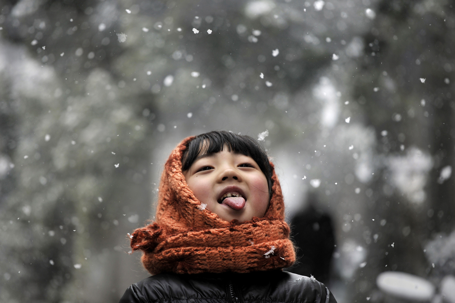 Feb. 13, 2014. A girl sticks out her tongue during snowfalls on a street in Hefei, Anhui province.