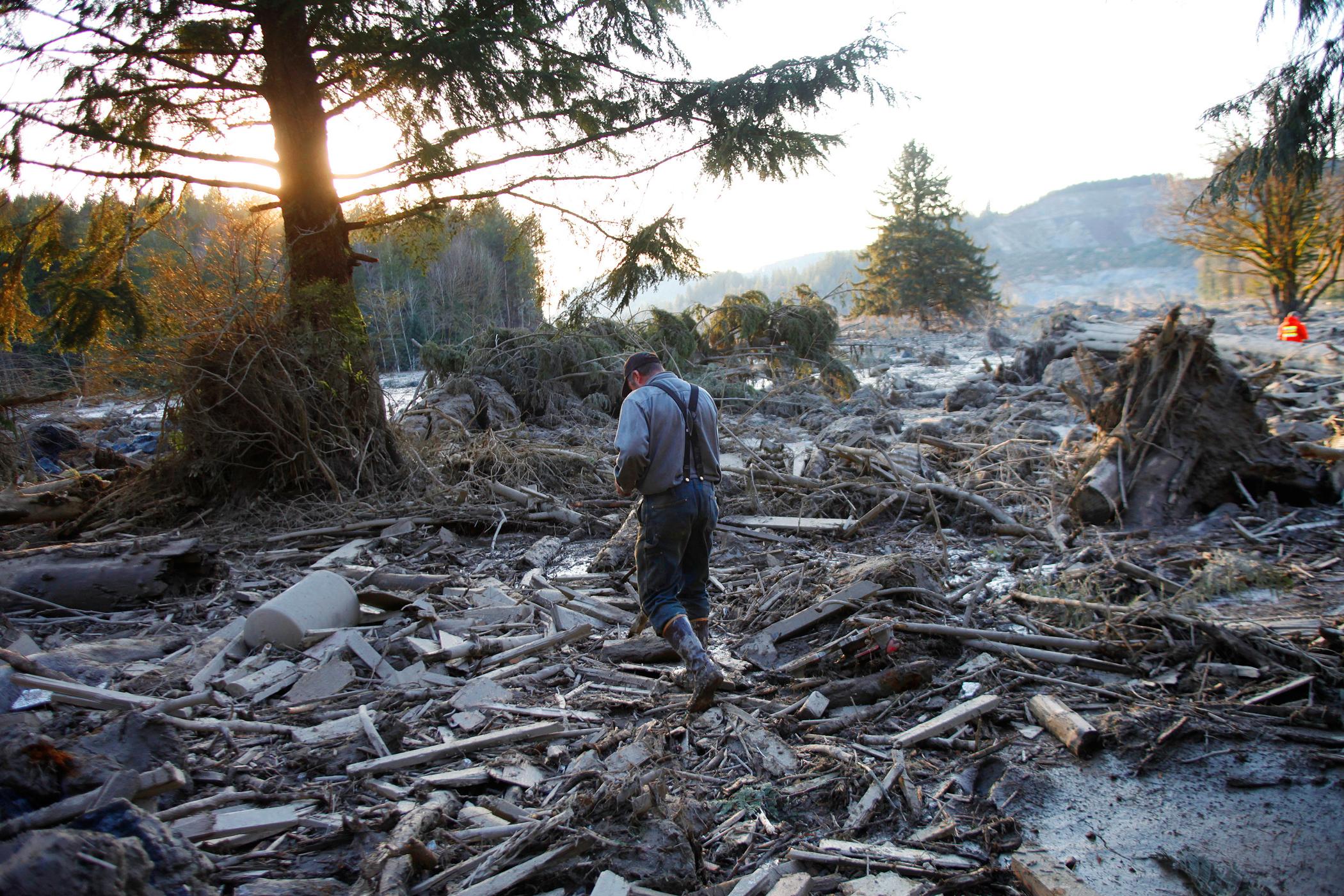 Steve Skaglund walks across the rubble on the east side of Saturday's fatal mudslide near Oso, Wash., Sunday, March 23, 2014.