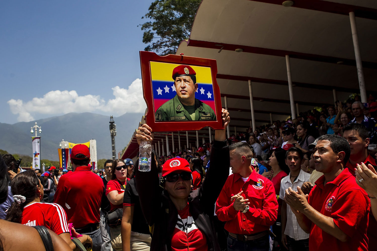A group of people carry the picture of late Venezuelan president Hugo Chavez, during the military parade to commemorate the first anniversary of the death of Chavez, in Caracas, March 5, 2014.