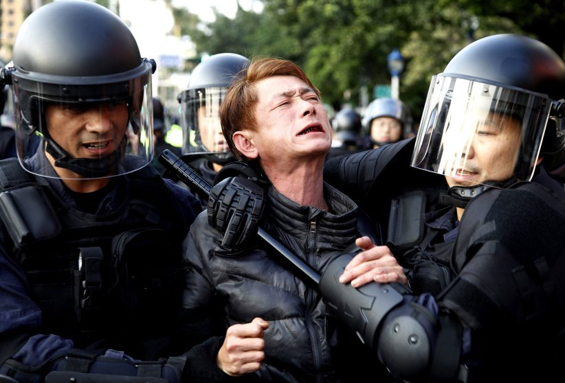 Riot police detain a protester near the Cabinet compound in Taipei, Taiwan, March 24, 2014.