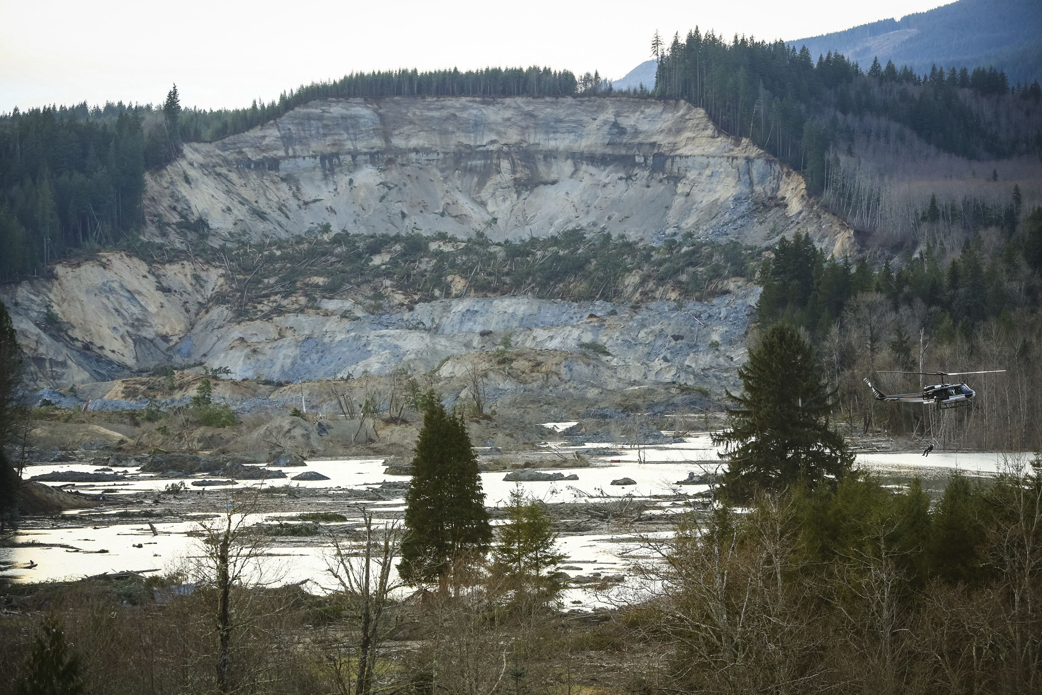 A rescue worker is lowered from a helicopter, right, near Oso, Wash, Monday, March 24, 2014.