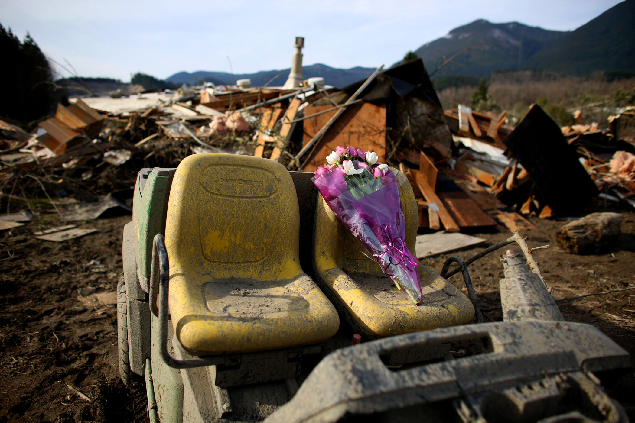 A bouquet of flowers left for victims sits perched on the seat of an abandoned vehicle in the wreckage of homes destroyed by Saturday's mudslide, Monday, March 24, 2014, near Oso, Wash.