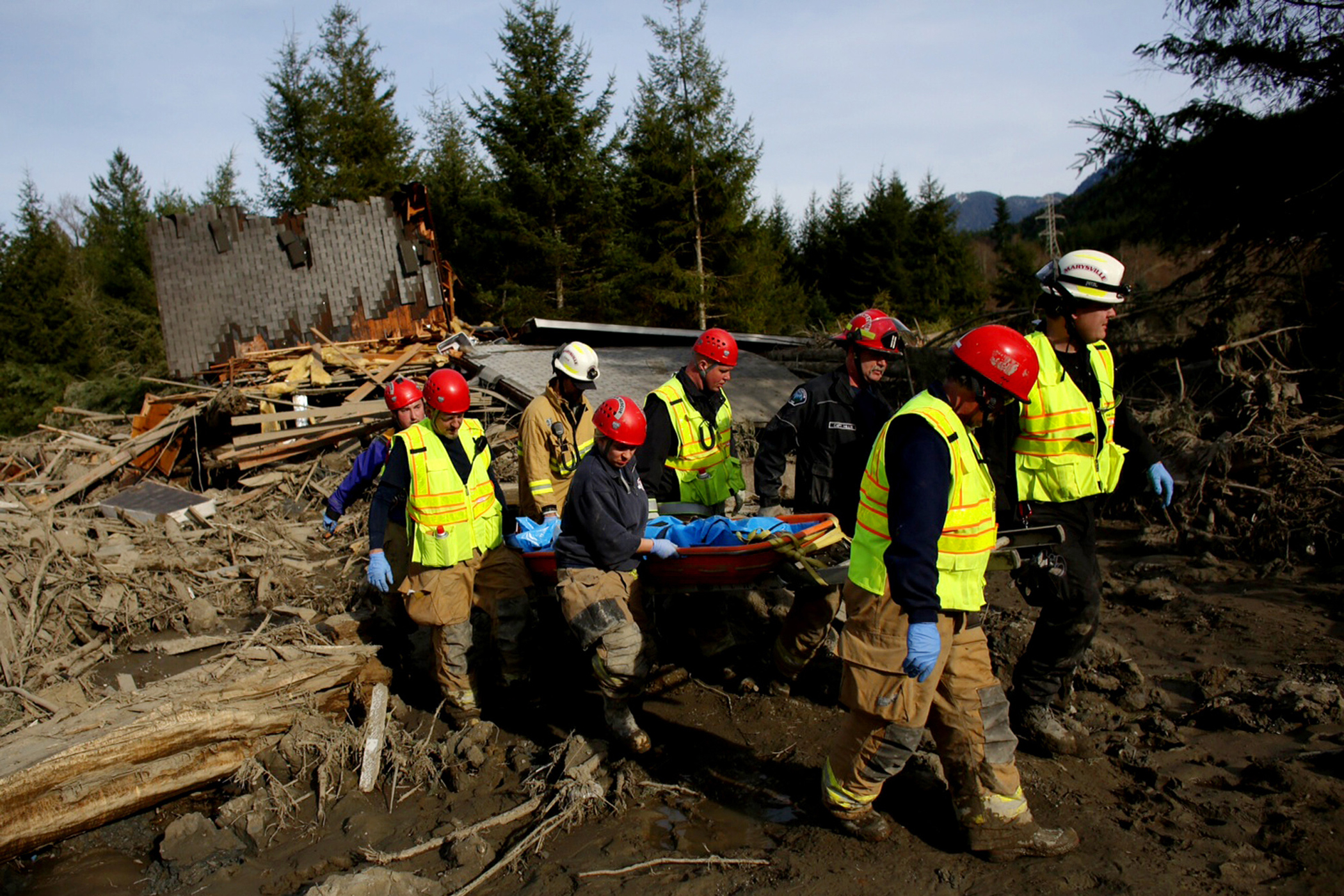 A search and rescue team brings out the tarp-covered body of a victim of Saturday's mudslide, Monday, March 24, 2014, near Oso, Wash.