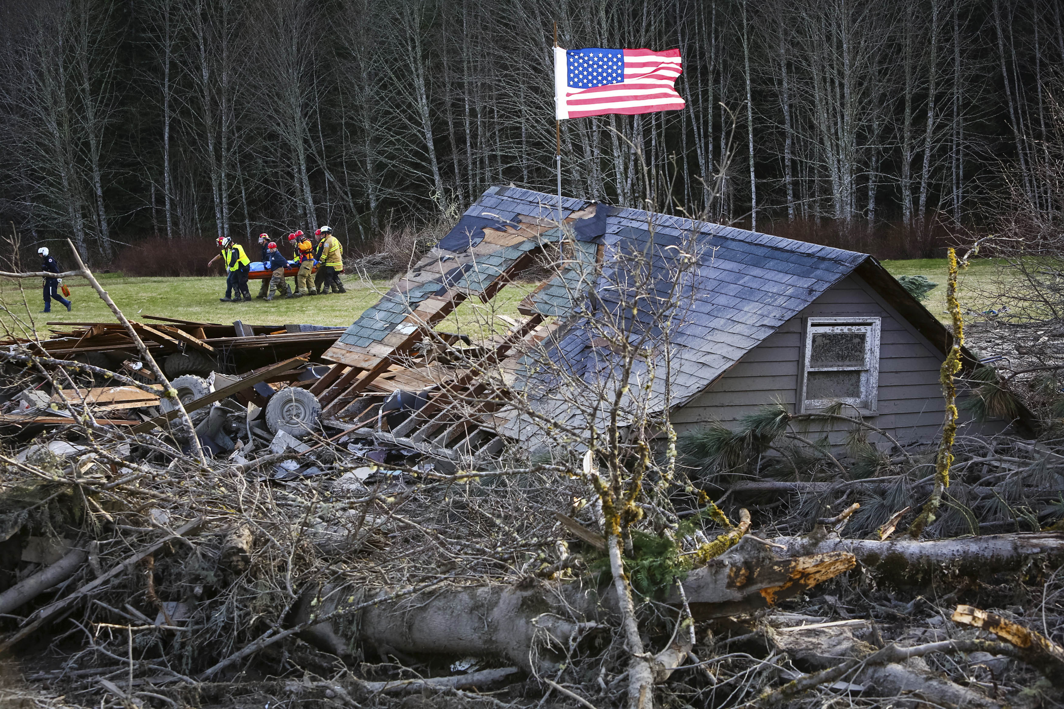 Rescue workers remove a body from the wreckage of homes destroyed by a mudslide near Oso, Wash, Monday, March 24, 2014.
