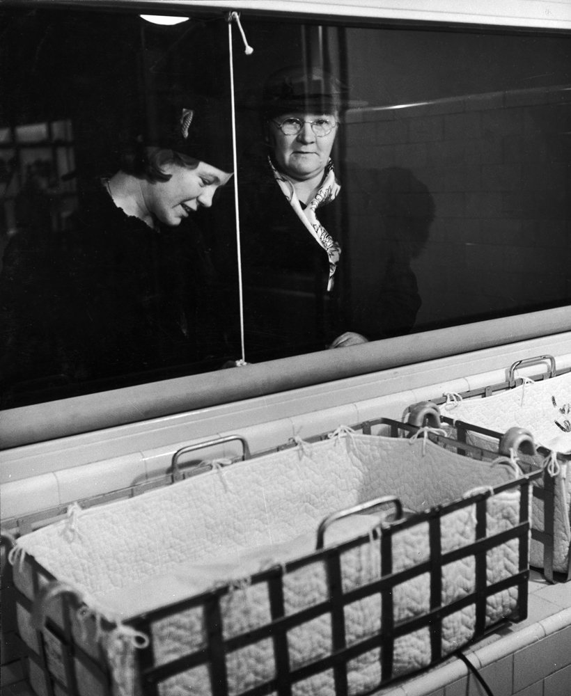 """<strong>Caption from LIFE.</strong> """"Mothers of premature babies are never allowed inside the nursery, can spend one hour a day fondly gazing at their infants in their cots through a glass partition."""""""