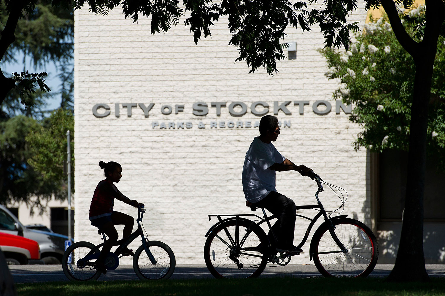 Pedestrians ride their bicycles along the street in Stockton, California, U.S., on June 14, 2012.