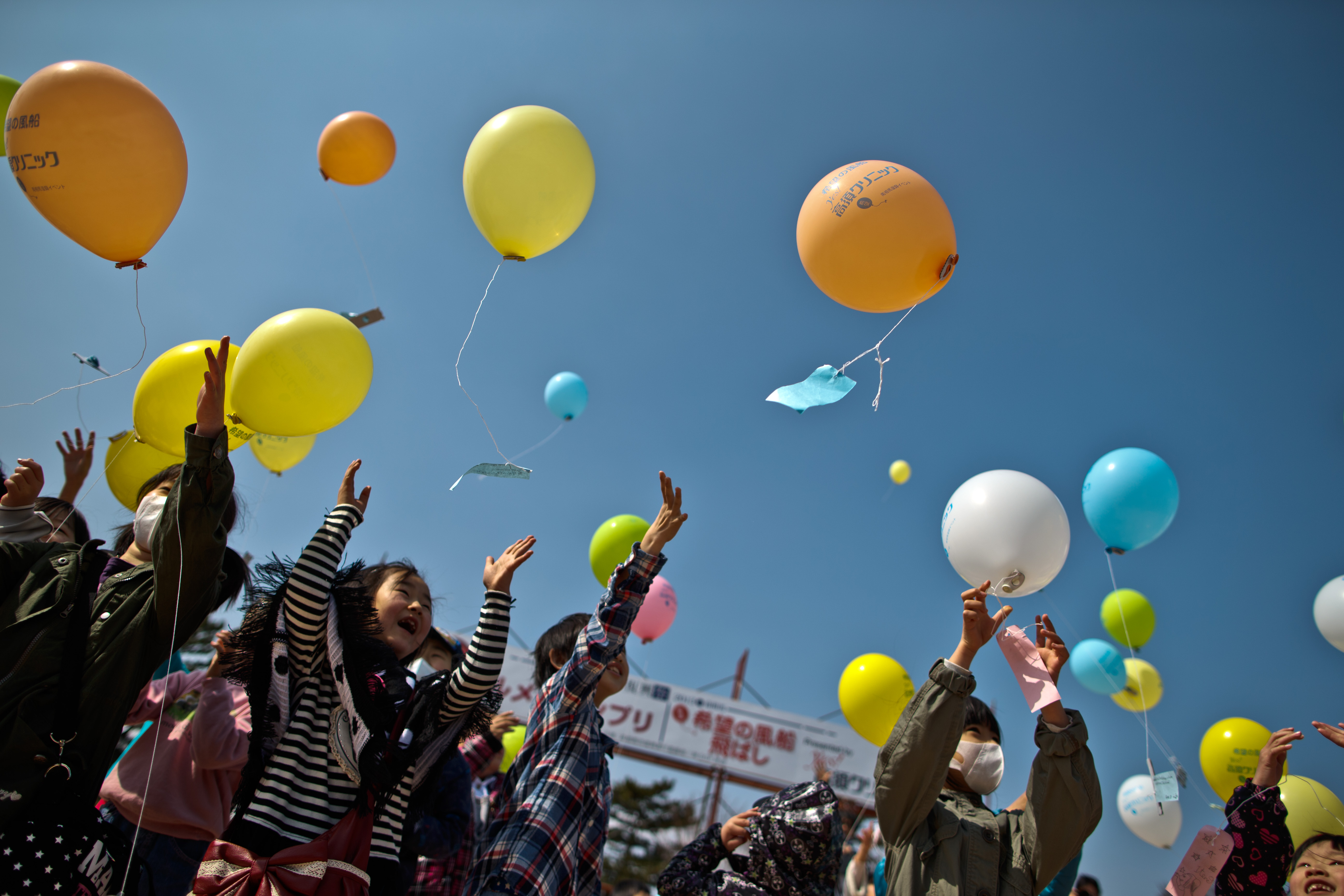 MINAMISOMA, JAPAN - MARCH 10:  Children float balloons and pay their respects to victims during the second anniversary commemoration of the earthquake and tsunami on March 10, 2013 in Minamisoma, Japan. Japan on March 11 will commemorate the second anniversary of the magnitude 9.0 earthquake and following tsunami, that claimed more than 18,000 lives.  (Photo by Athit Perawongmetha/Getty Images)