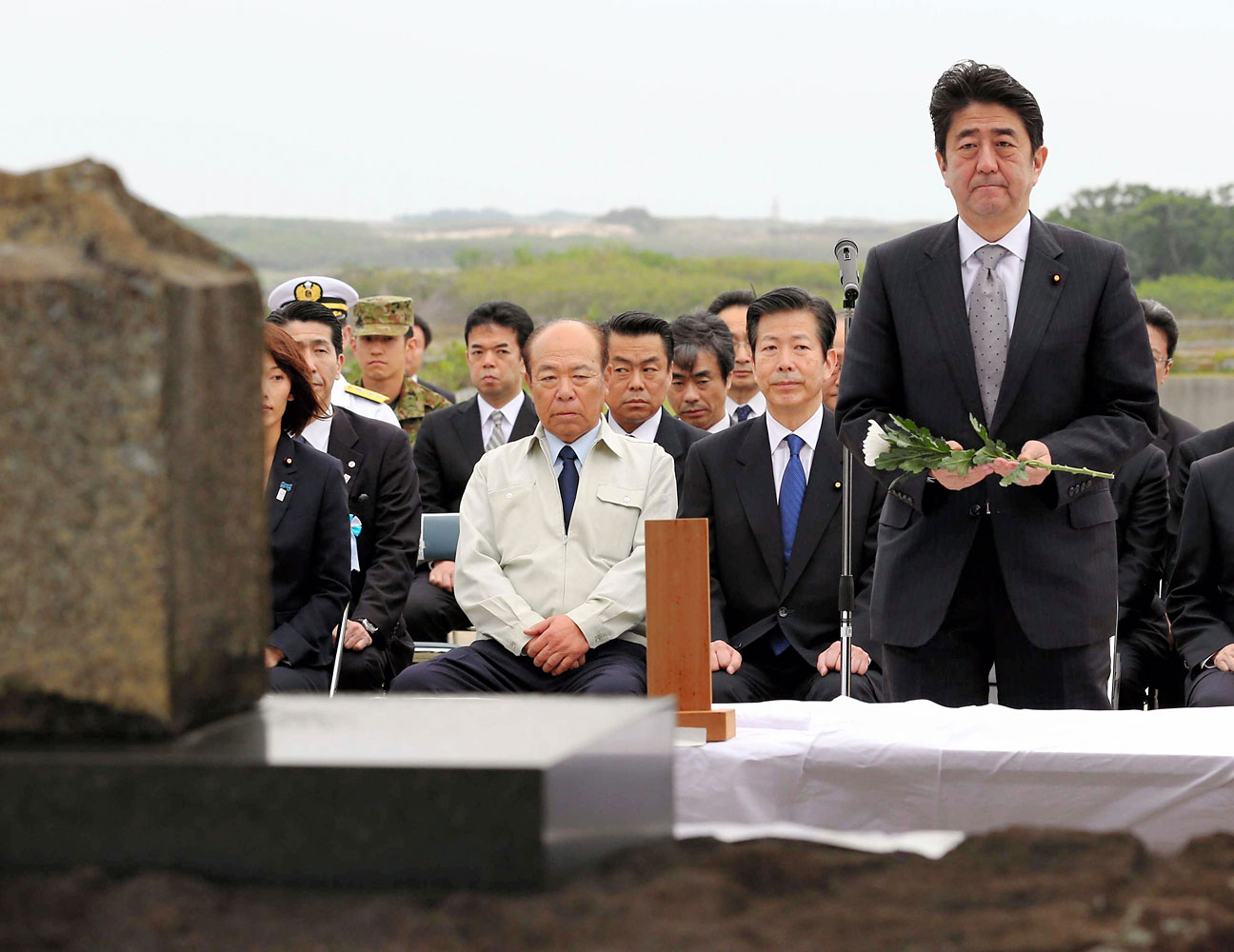 Japanese Prime Minister Shinzo Abe offers a flower durinf a memorial service to commemorate the war deads of the World War II at Iwo Island on April 14, 2013 in Ogasawara, Tokyo, Japan.