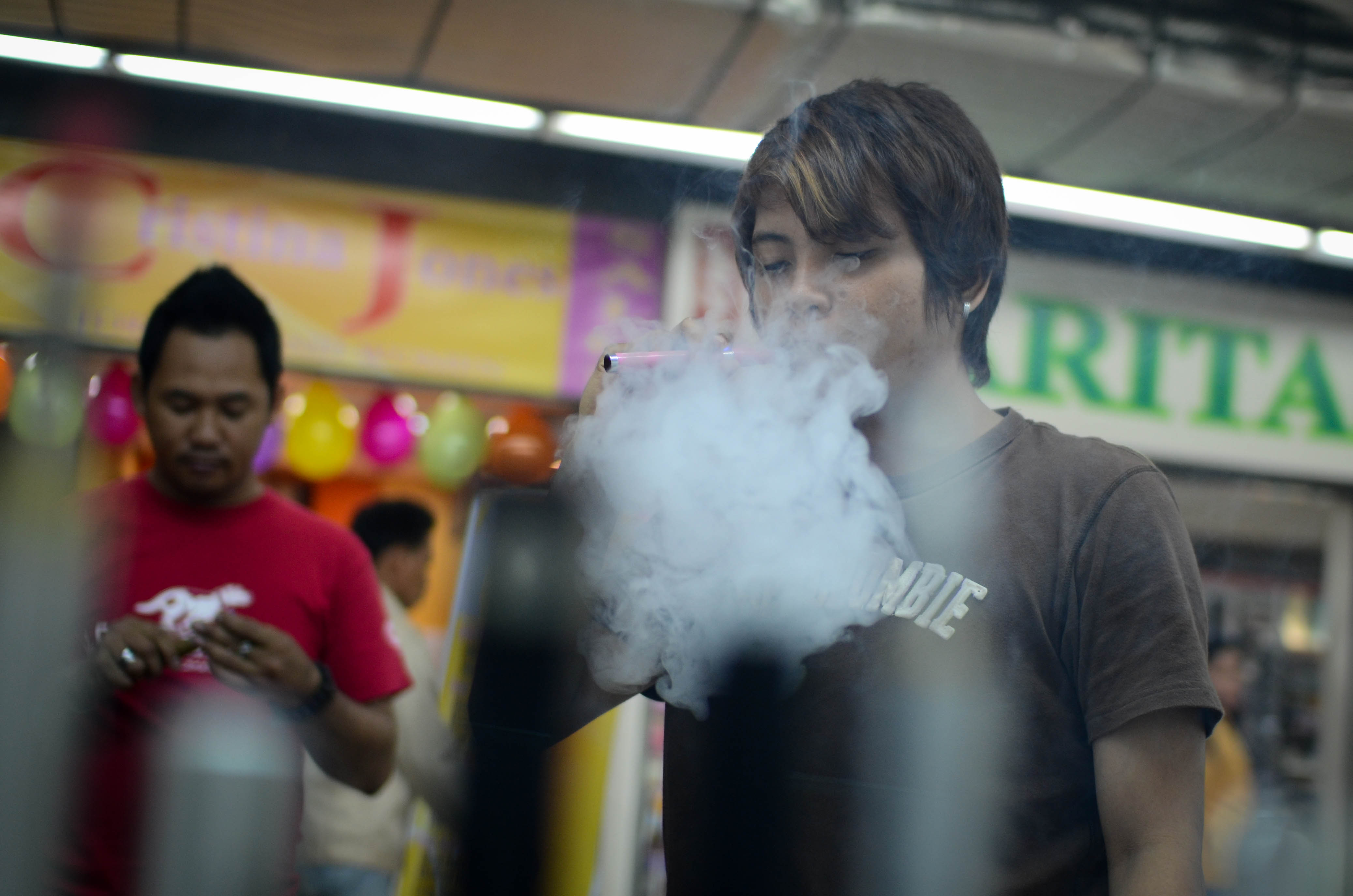 Consumers smoke electronic cigarettes at a mall on June 30, 2013 in Manila, Philippines.