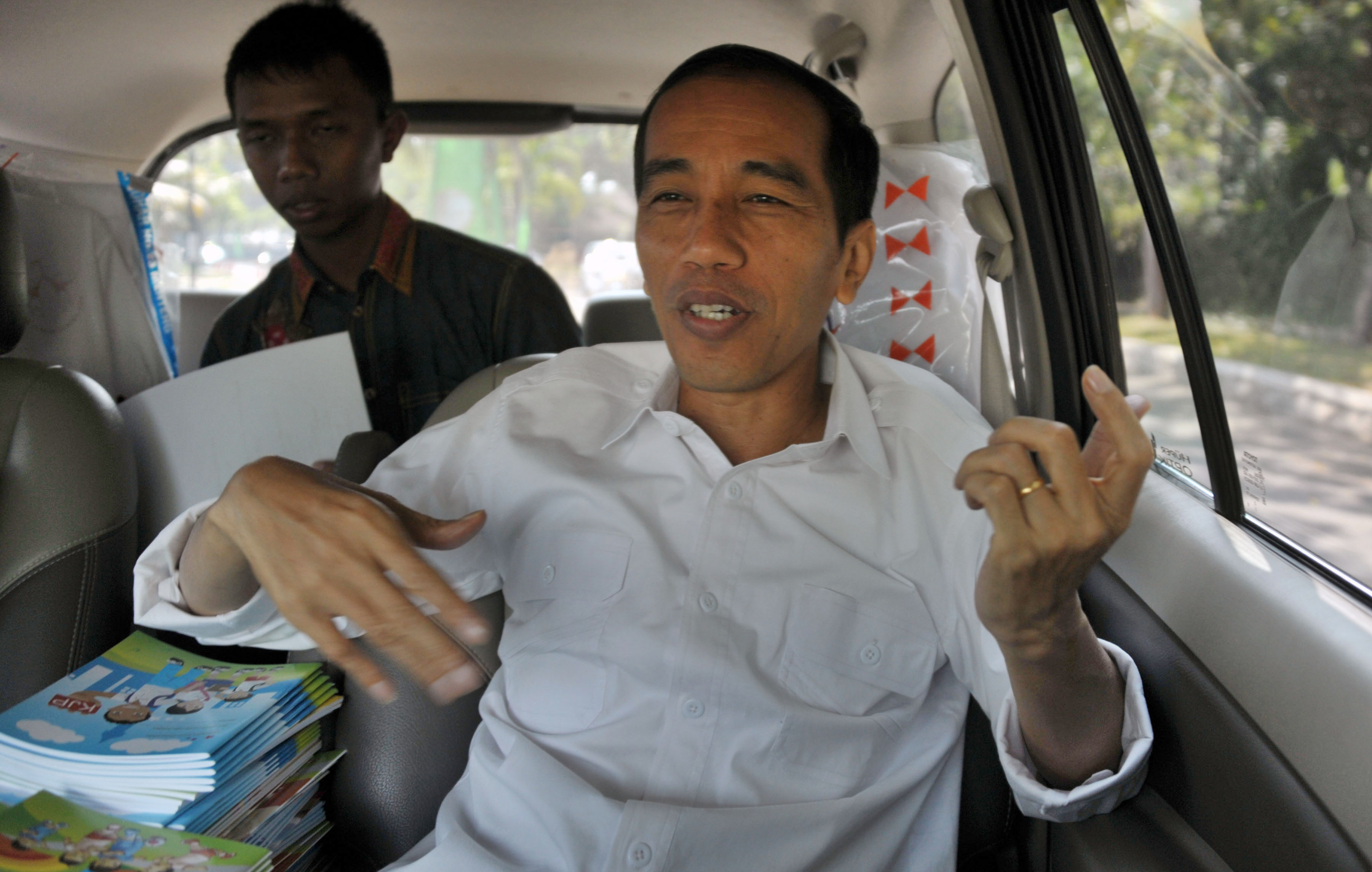 This picture taken on August 22, 2013, Jakarta governor Joko Widodo, a rock fan makes an air guitar gesture as he travels on a van on the way to make sight inspection in Jakarta city.