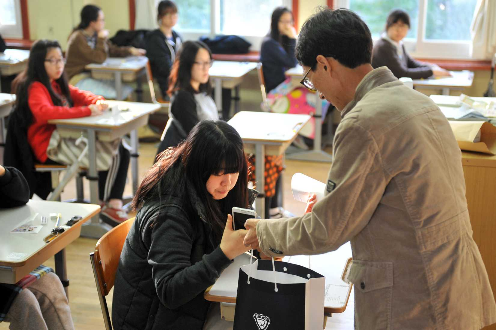 An examination invigilator (R) collects mobile phones from South Korean students before they take the College Scholastic Ability Test, a standardised exam for college entrance, at a high school in Seoul on November 7, 2013.