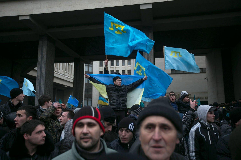 Crimean Tatars hold flags during rallies near the Crimean parliament building in Simferopol, Feb. 26, 2014.