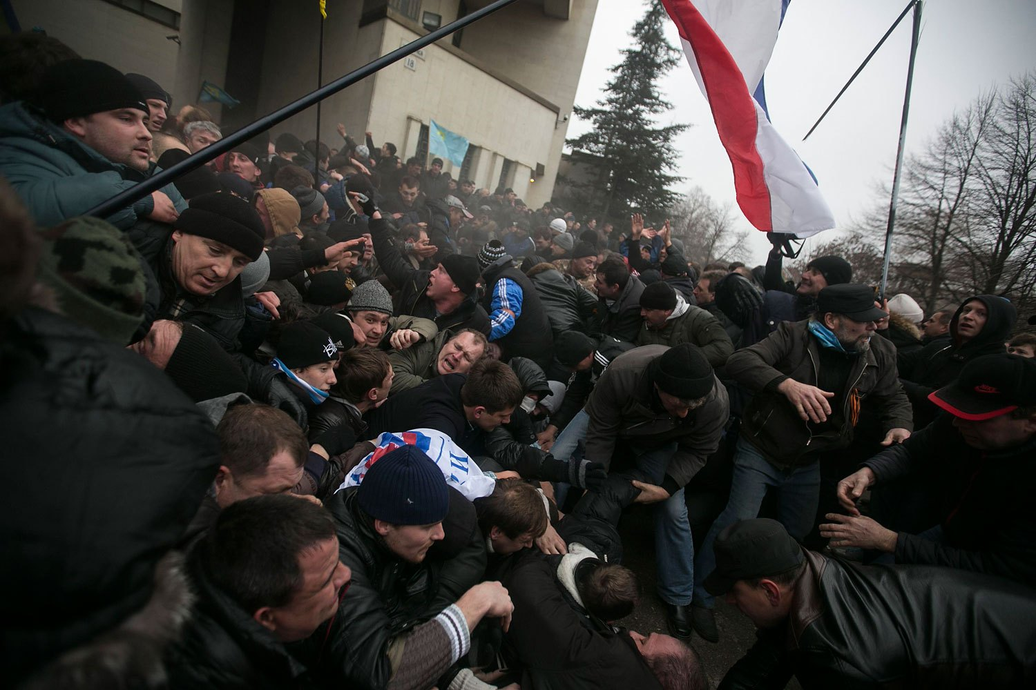 Ukrainian men help pull one another out of a stampede beneath a flag of Crimea during clashes at rallies held by ethnic Russians and Crimean Tatars near the Crimean parliament building in Simferopol Feb. 26, 2014.
