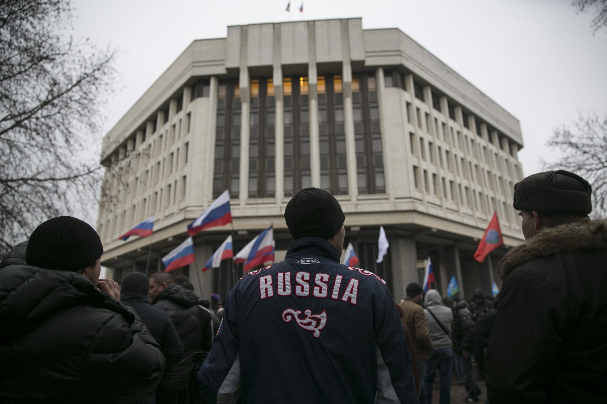 Men stand during a pro-Russian rally outside the Crimean parliament building in Simferopol, Feb. 27, 2014.