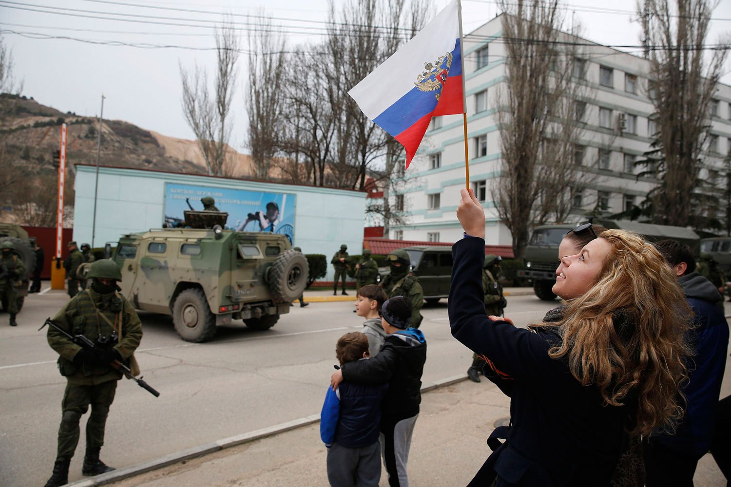 A woman waves a Russian flag as armed servicemen wait near Russian army vehicles outside a Ukrainian border guard post in the Crimean town of Balaclava, March 1, 2014.