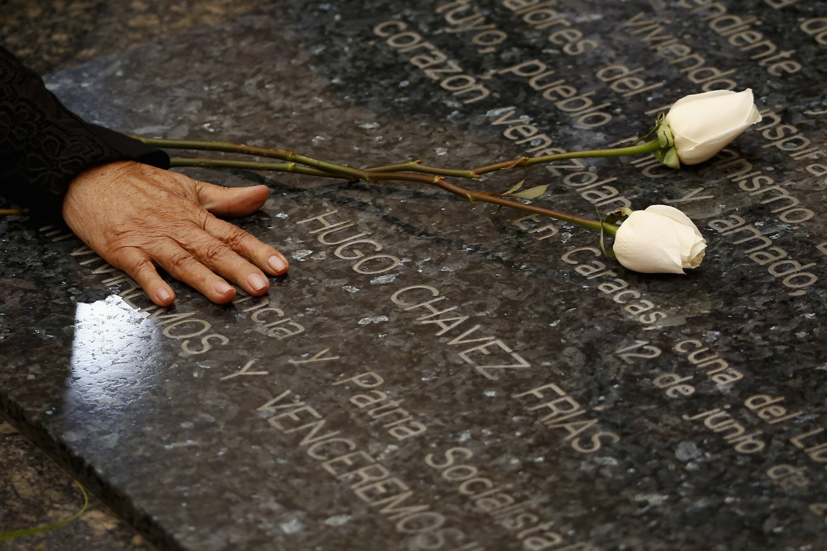 Elena Frias, mother of Venezuela's late president Hugo Chavez, puts flowers over his tomb during the first anniversary of his death in Caracas, March 5, 2014.