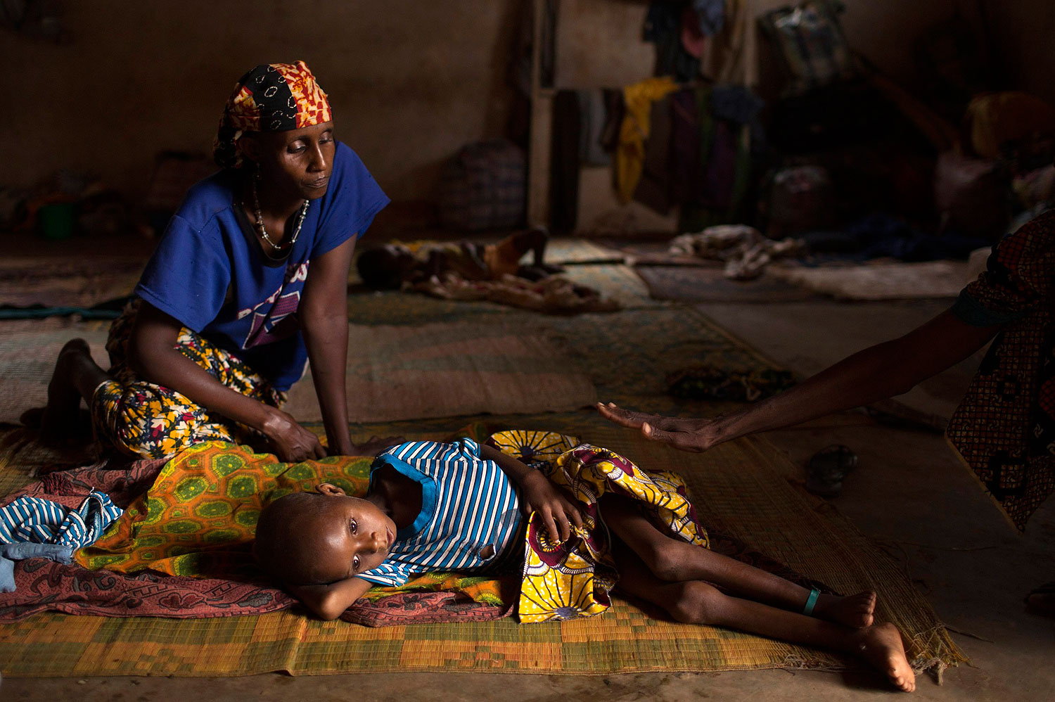 Relatives sit near Aliou Abalaye, 4, as he lies sick on the floor near Kilometre 12 (PK12), in Bangui, Central African Republic, where internally displaced Muslims are stranded due to the ongoing sectarian violence, on March 6, 2014.