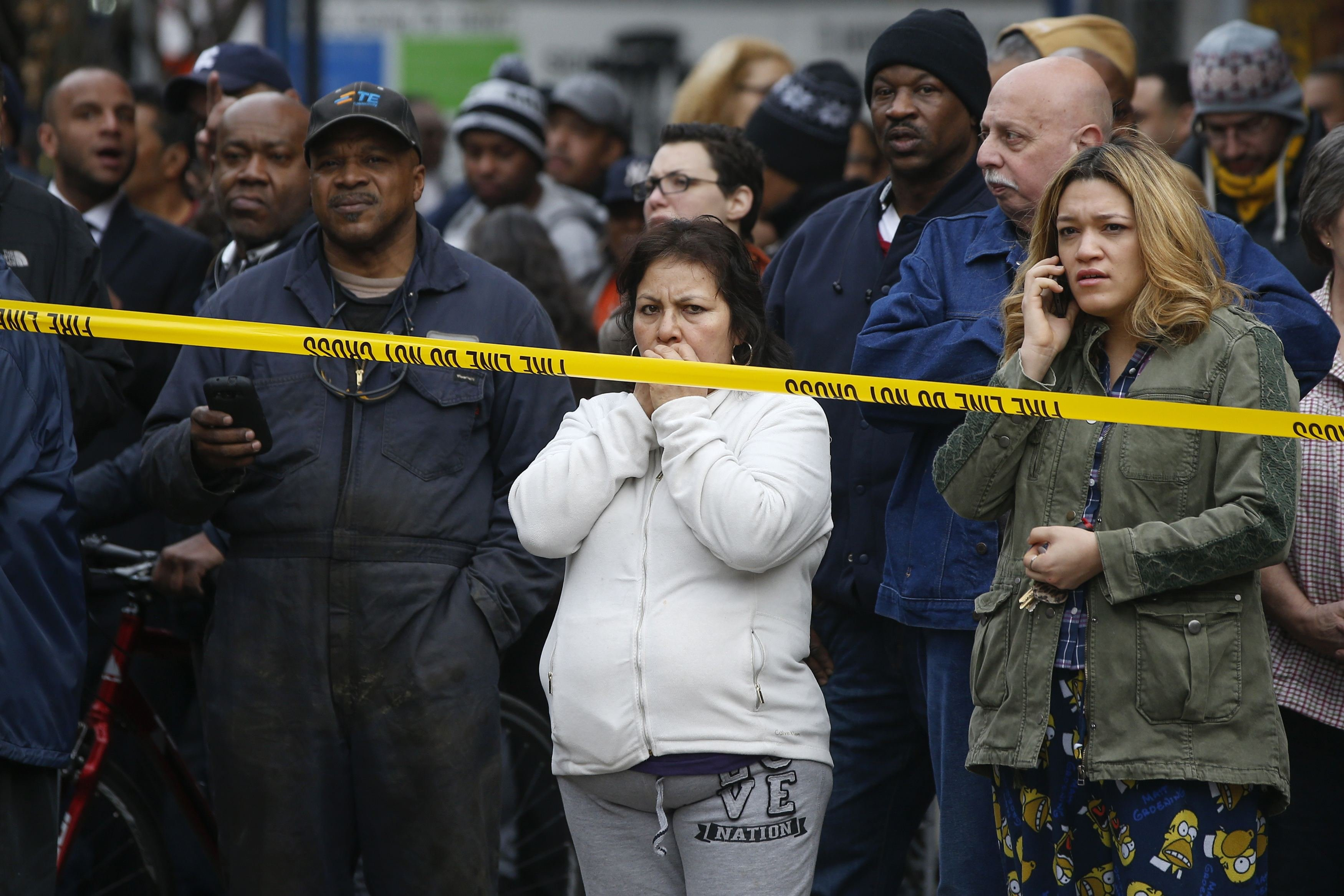 Residents watch as firefighters work at the scene of a building collapse in New York, March 12, 2014.
