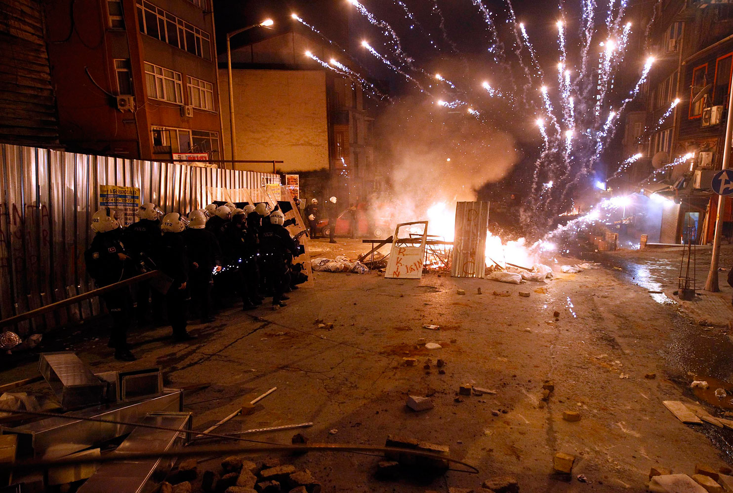 Riot policemen shield themselves as fireworks thrown by anti-government protesters explode near central Taksim square in Istanbul March 12, 2014.