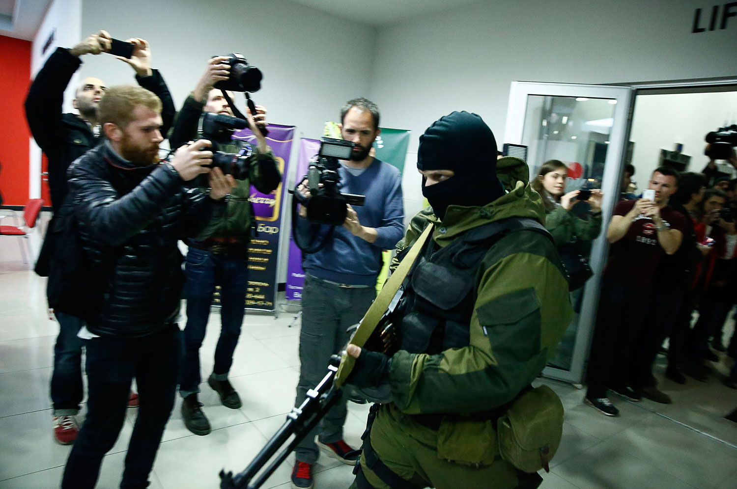 An armed man leaves the Moscow hotel in Simferopol, March 15, 2014.