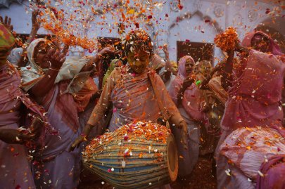 Widows dance as they throw flowers into the air during Holi celebrations organised by non-governmental organisation Sulabh International at a widows' ashram in Vrindavan in the northern Indian state of Uttar Pradesh, March 17, 2014.