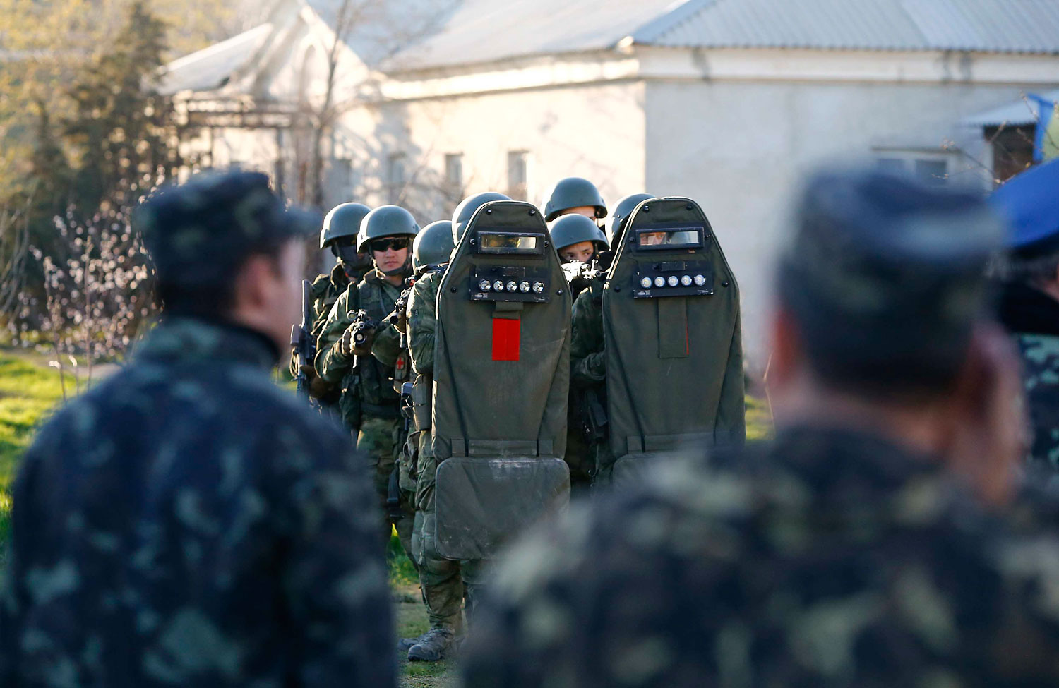 Armed men, believed to be Russian servicemen, stand guard, with Ukrainian servicemen seen in the foreground, at a military airbase, in the Crimean town of Belbek near Sevastopol March 22, 2014.