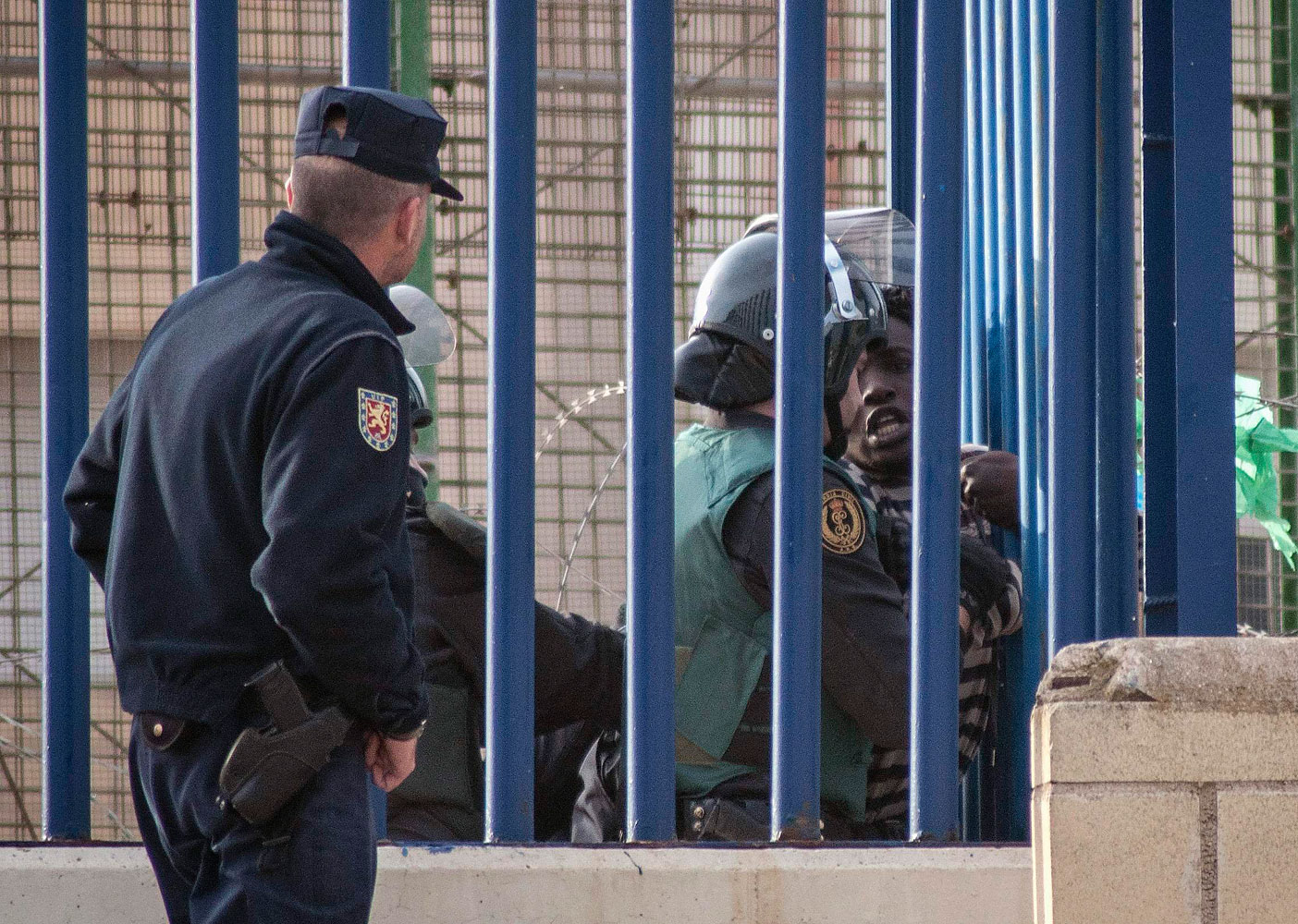 An African migrant is detained by a Spanish civil guard at the border fence near Beni Enza between Morocco and Spain's north African enclave Melilla while attempting to cross into Spanish territory, March 28, 2014.