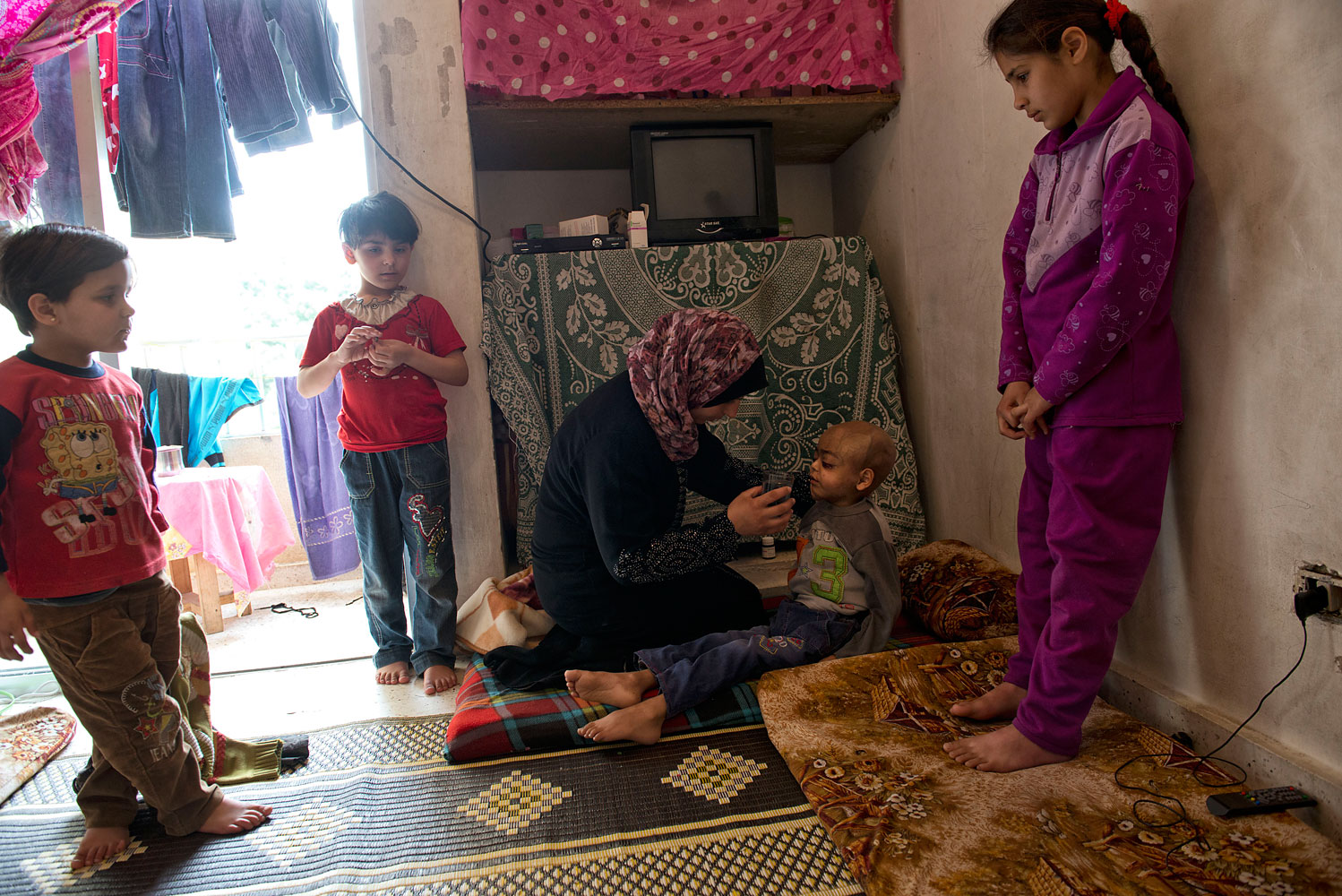 Feryal Delly, a Syrian refugee, gives water to her 4-year-old son Zacharia on March 9. Zacharia, who has a brain tumor, lives with his family in a rented apartment in Halat, north of Beirut.