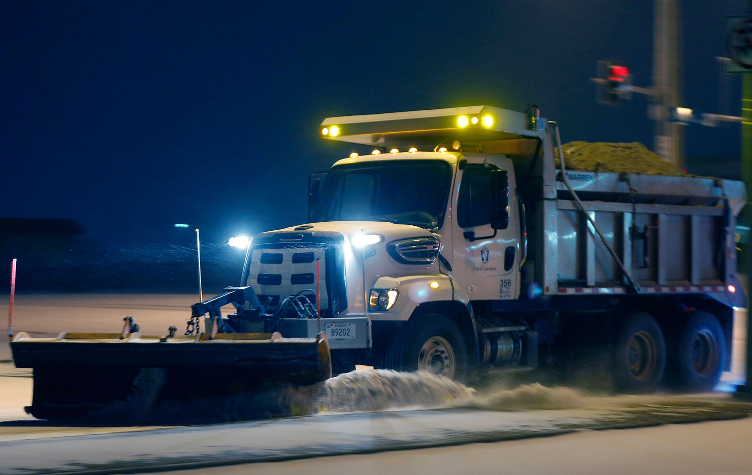 A city plow removes snow from an intersection along 6th Street in Lawrence, Kan., March 2, 2014.
