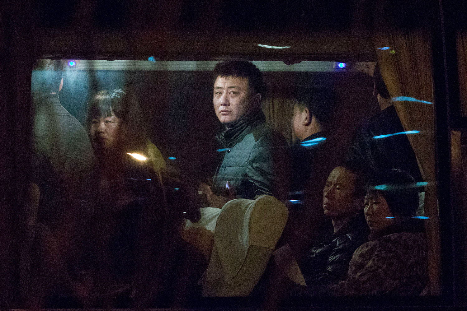 Relatives of Chinese passengers aboard a missing Malaysia Airlines plane wait on a bus in Beijing on March 9, 2014, to get paperwork to fly to Malaysia