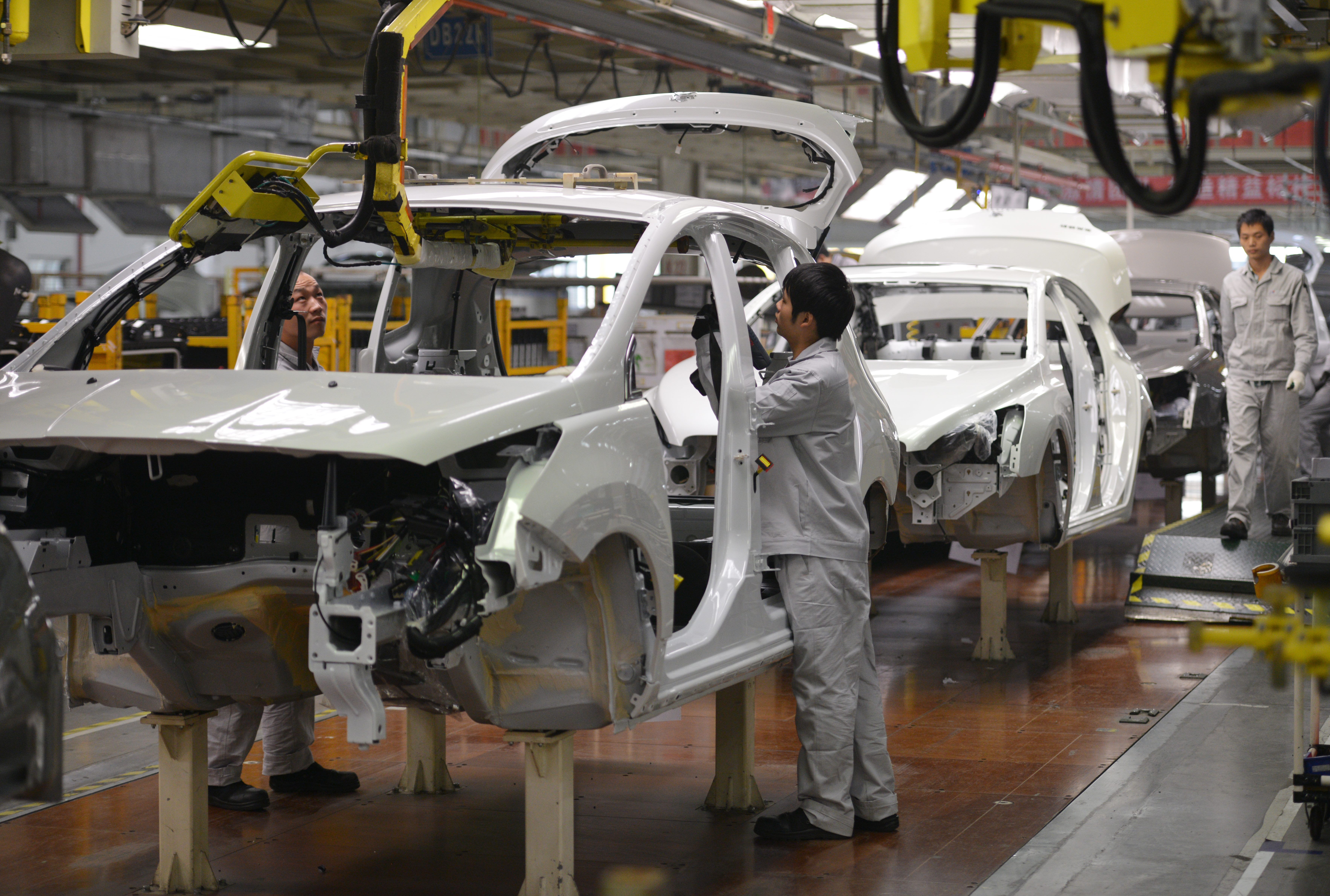 Workers on the assembly line at the Sino-French joint venture Dongfeng Peugeot-Citroën Automobile (DPCA) plant in Wuhan in China's central Hubei province, Dec. 2013.