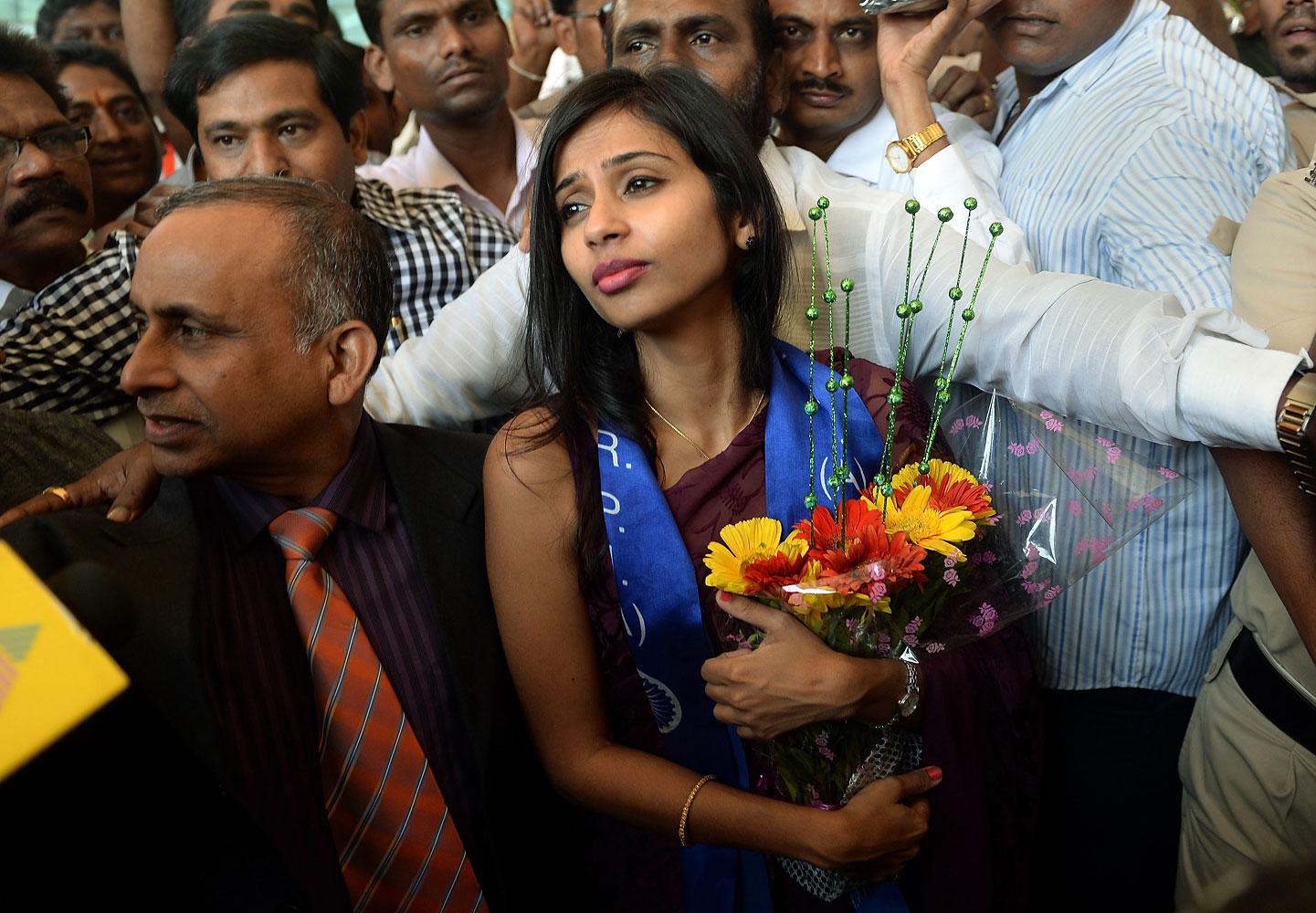 Indian diplomat Devyani Khobragade, center, accompanied by her father Uttam Khobragade, arrives at the domestic airport in Mumbai on Jan. 14, 2014.