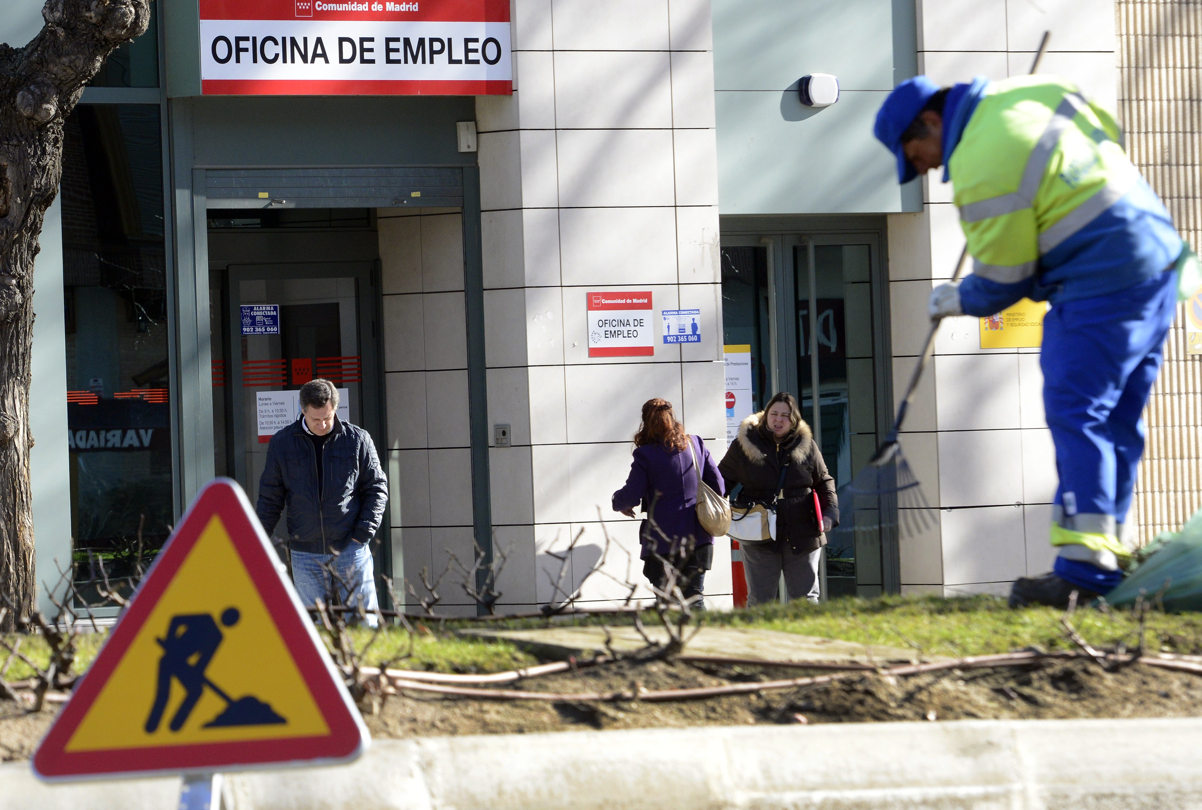 A municipal worker cleans the ground as people walk outside a government employment office in Madrid on January 23, 2014.