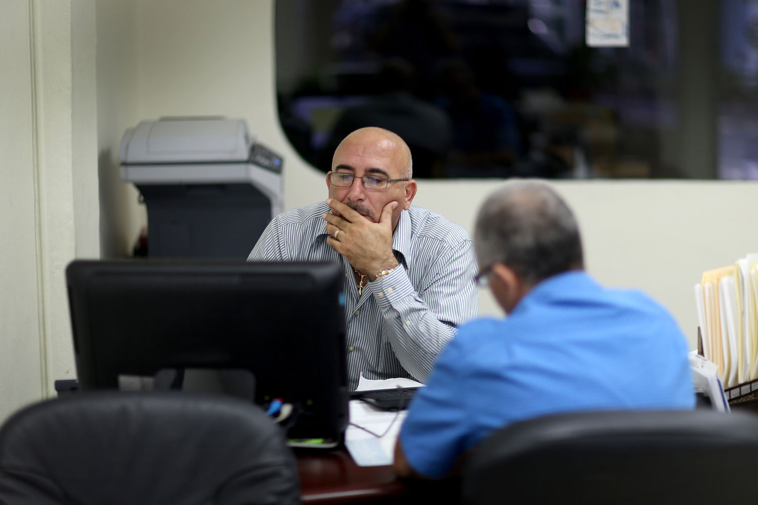 A. Michael Khoury at Leading Insurance Agency enrolls Hisham Uadadeh in a health insurance plan under the Affordable Care Act on Feb. 13, 2014 in Miami.
