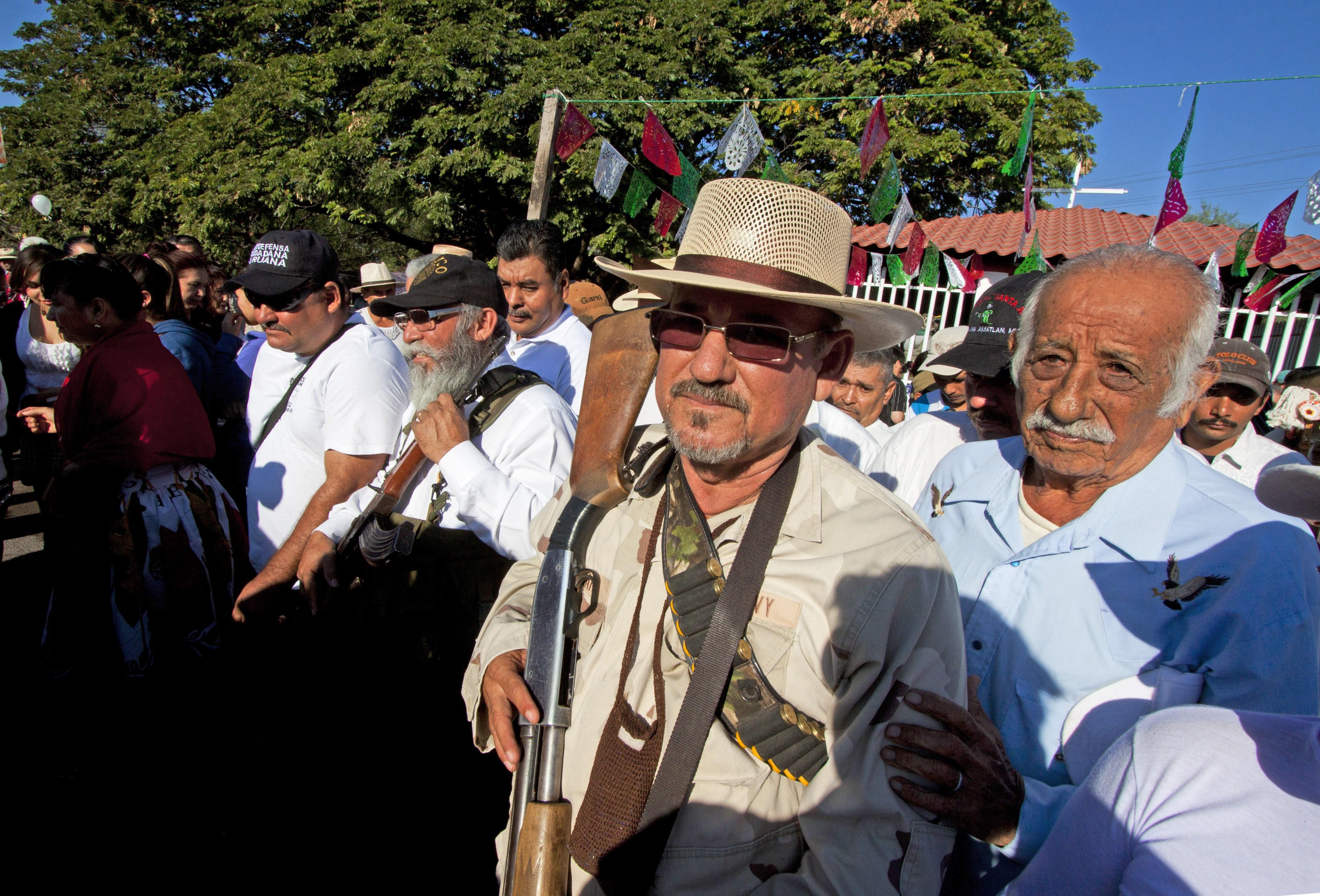 Hipolito Mora (C), leader of the self-protection militia walks in La Ruana community, state of Michoacan, Mexico, on February 24, 2014.