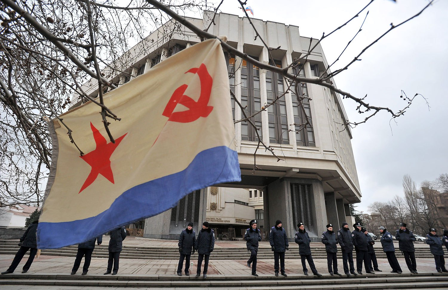 A flag of the Russian Navy hangs from a tree as policemen stand guard in front of the local parliament building on Feb. 28, 2014 in Simferopol.
