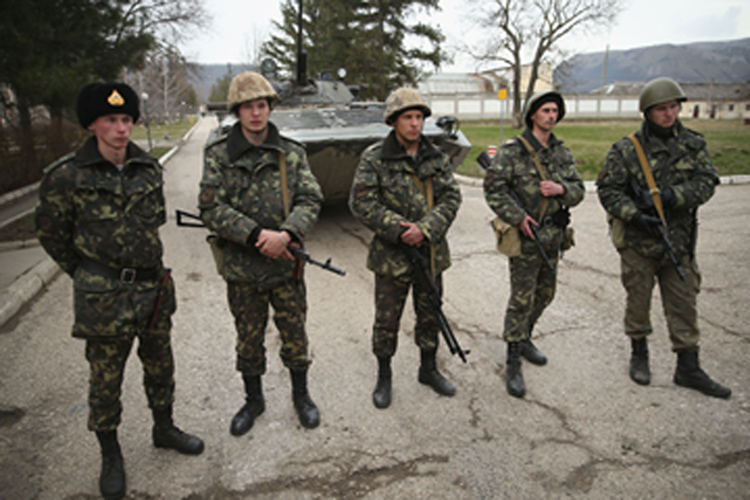 Ukrainian soldiers and a Ukrainian army tank stand just inside the gate at a Ukrainian military base that was surrounded by several hundred Russian-speaking soldiers in Crimea on March 2, 2014 in Perevanie, Ukraine.