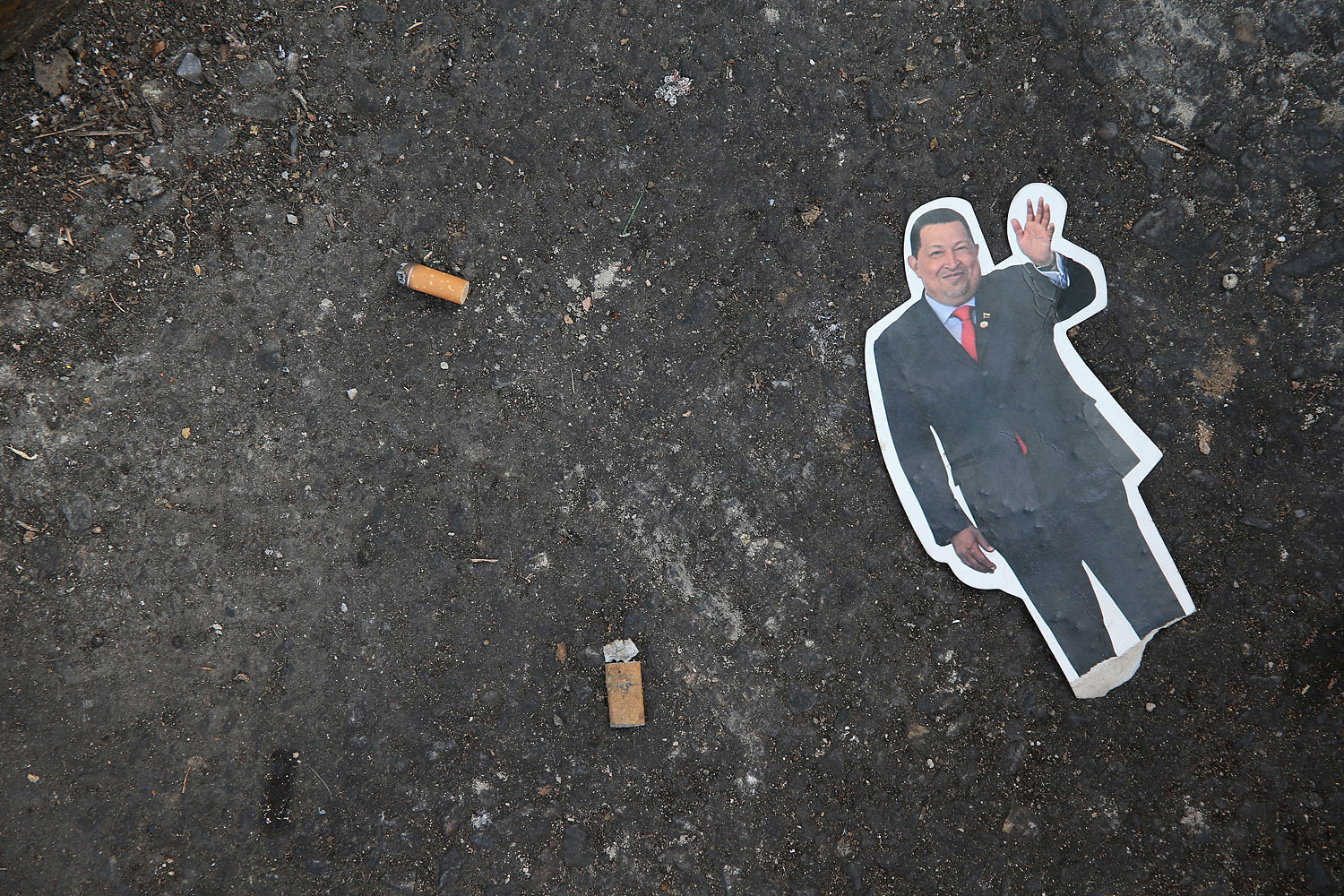 A cutout of former Venezuelan President Hugo Chavez lies on the street following a parade marking the first anniversary of his death on March 5, 2014 in Caracas.