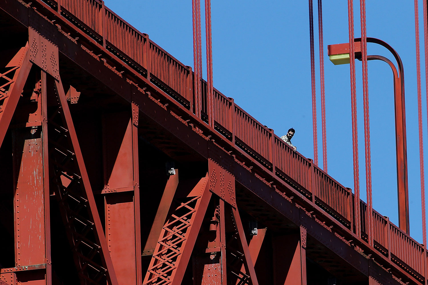 A visitor looks over the railing on the Golden Gate Bridge on March 12, 2014 in San Francisco.