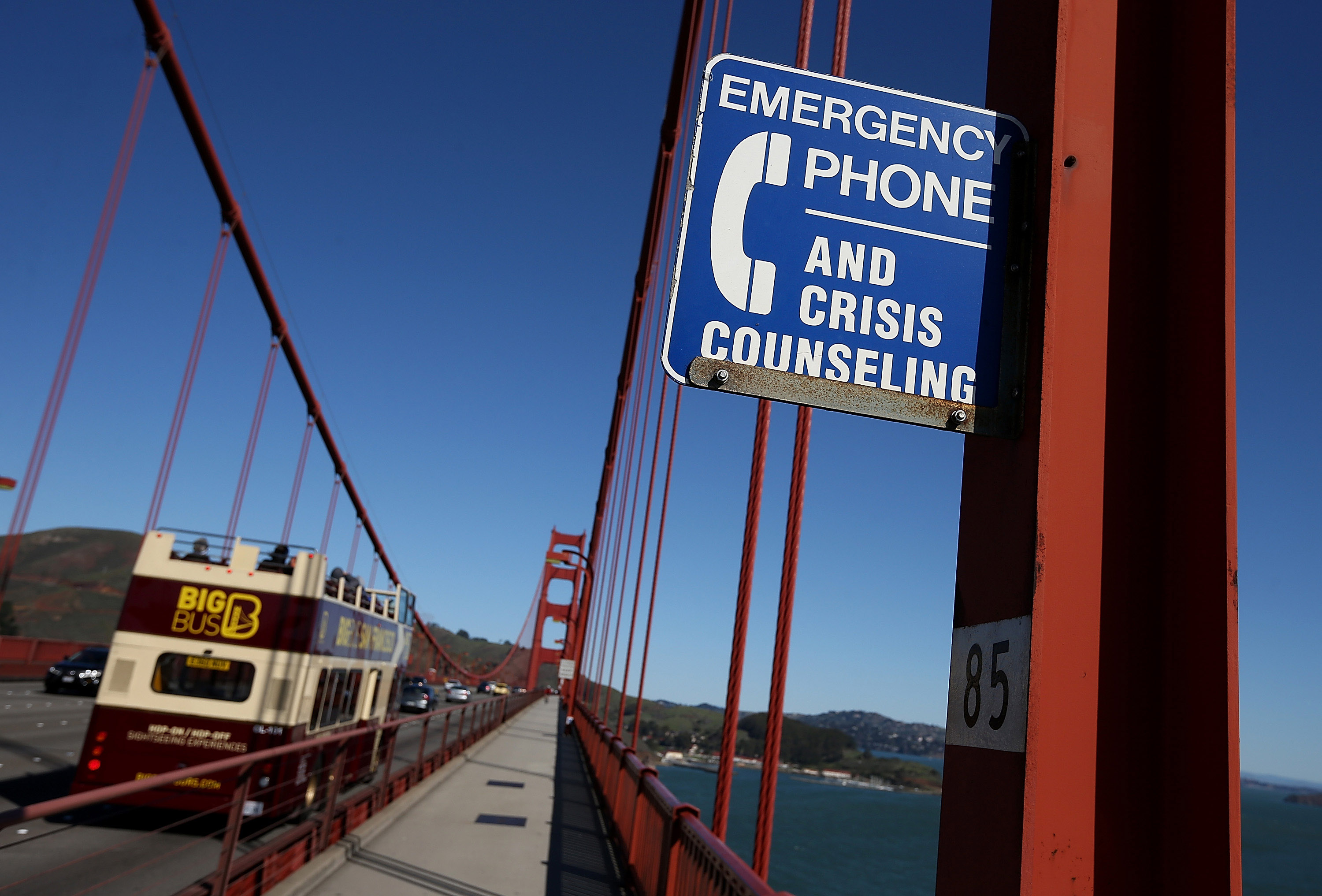 A sign alerting people to use an emergency crisis counseling phone if in distress.