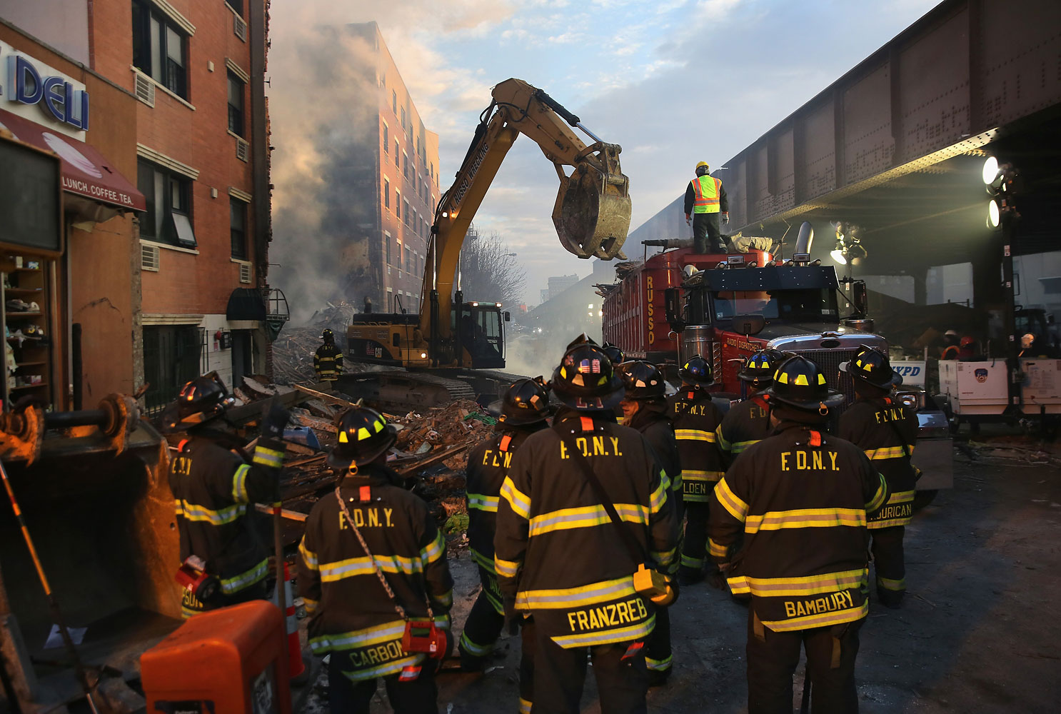 NEW YORK, NY - MARCH 13:  Firemen watch as work crews remove debris from the site of an explosion in East Harlem on March 13, 2014 in New York City. At least 7 people were killed, according to reports, in Wednesday's explosion which collapsed two buildings on Park Avenue at 116th Street.