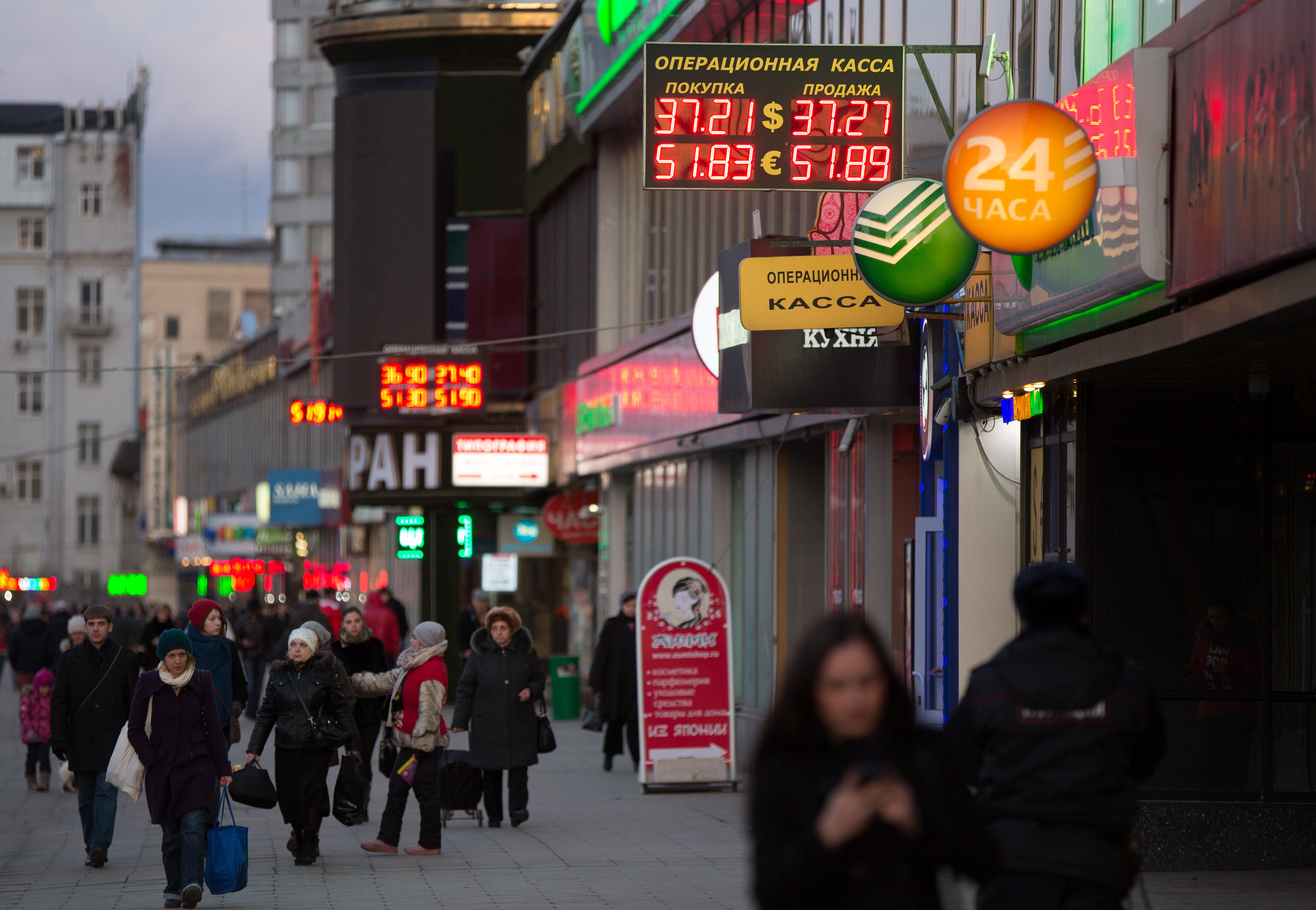Pedestrians pass illuminated signs advertising foreign exchange rates for dollars, rubles and euros on a street in Moscow on March 17, 2014. Russian stocks have slumped 14% this month as the Ukraine crisis intensified