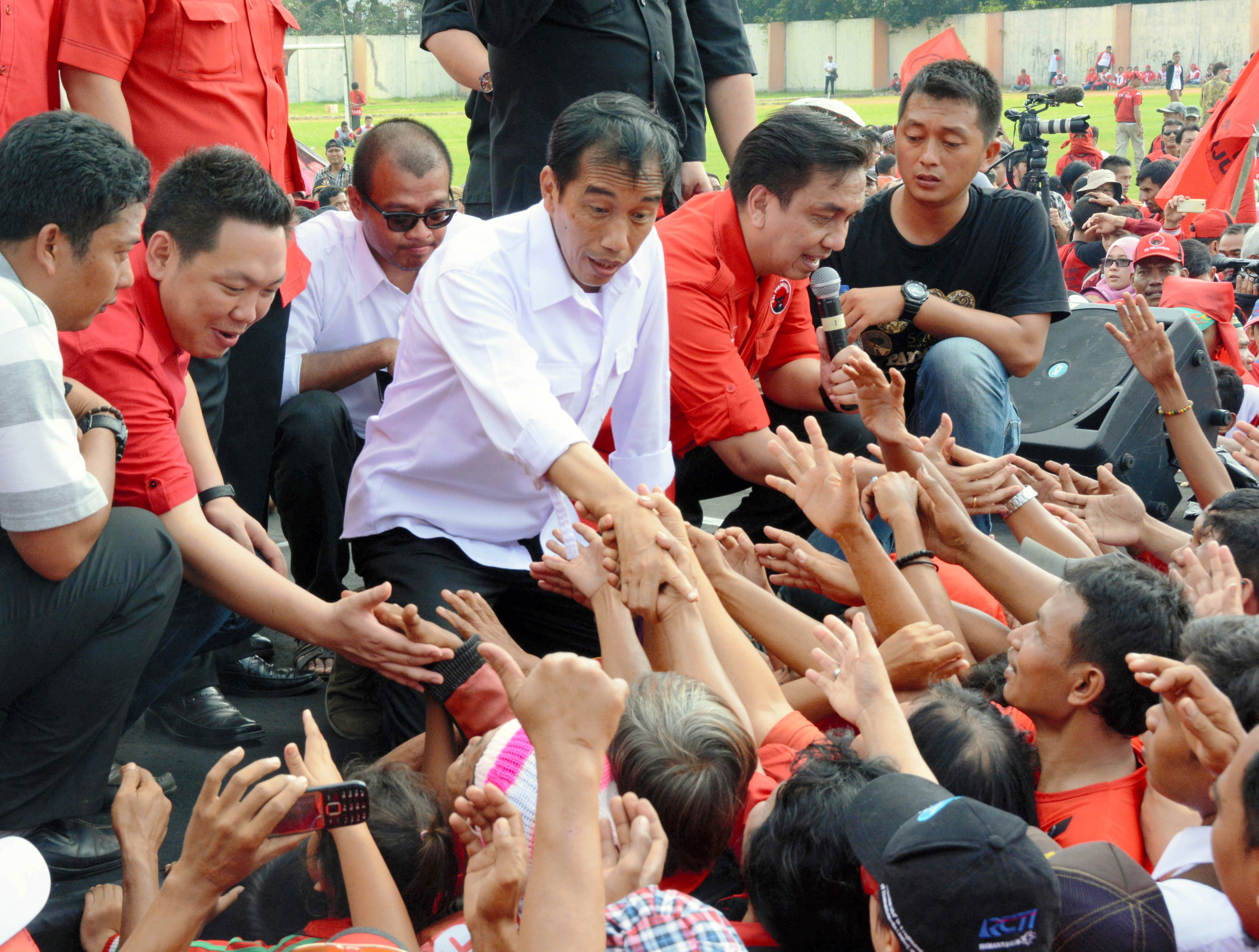 Indonesian presidential candidate and Jakarta Governor Joko Widodo, center, shakes hands with his supporters after making a speech in Jakarta as the election campaign kicks off on March 16, 2014