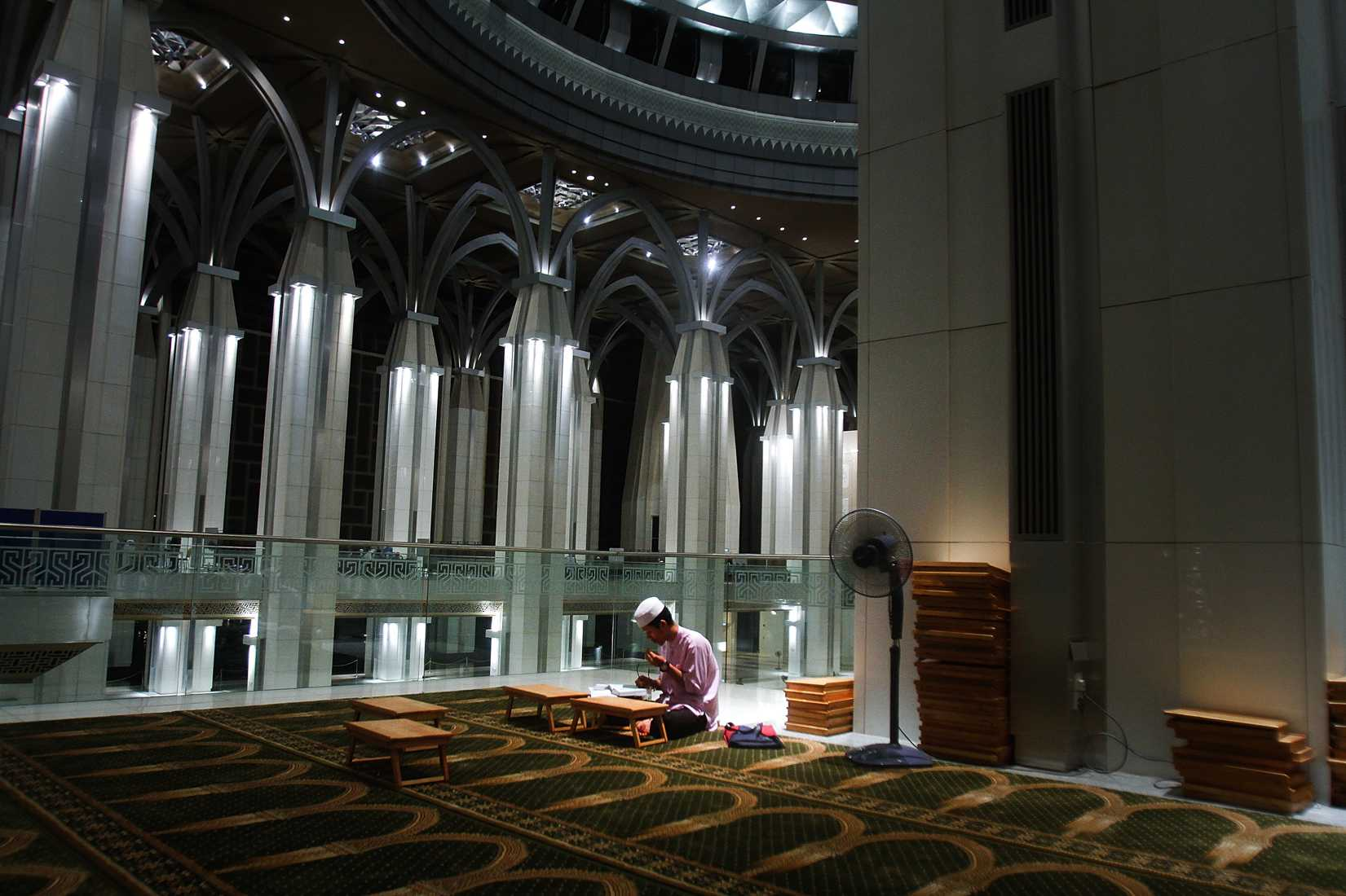 A man recites the Koran after a special prayers held for the missing Malaysian airliner MH370, March 18, 2014 in Kuala Lumpur, Malaysia.