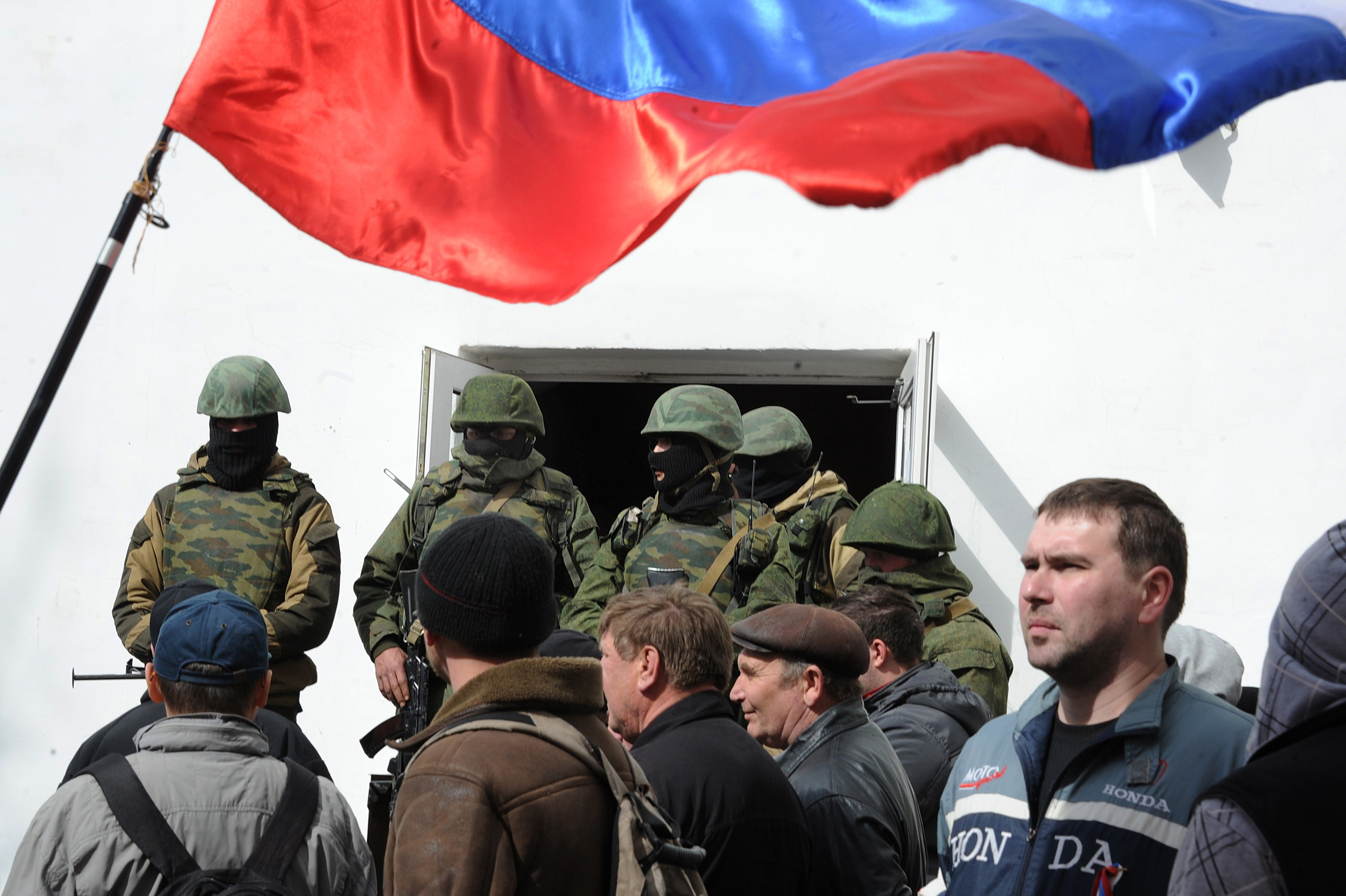 Russian soldiers and pro-Russian self-defence activists patrol at the Ukrainian navy headquarters in the Crimean city of Sevastopol on March 19, 2014.