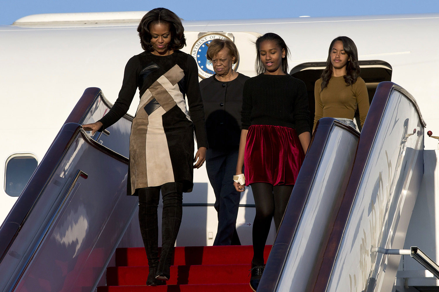 Michelle Obama, her daughters Sasha and Malia, and Michelle Obama's mother Marian Robinson exit their plane upon arrival at Beijing's Capital International Airport on March 20, 2014.