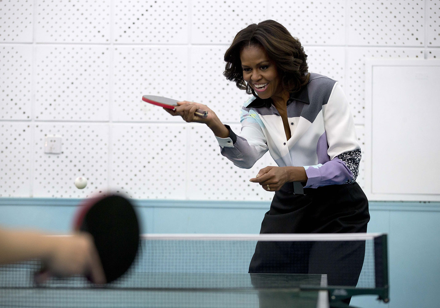 Sporting an eclectic top, Obama plays table tennis during her visit to the Beijing Normal School, a school that prepares students to attend university abroad, March 21, 2014 in Beijing.