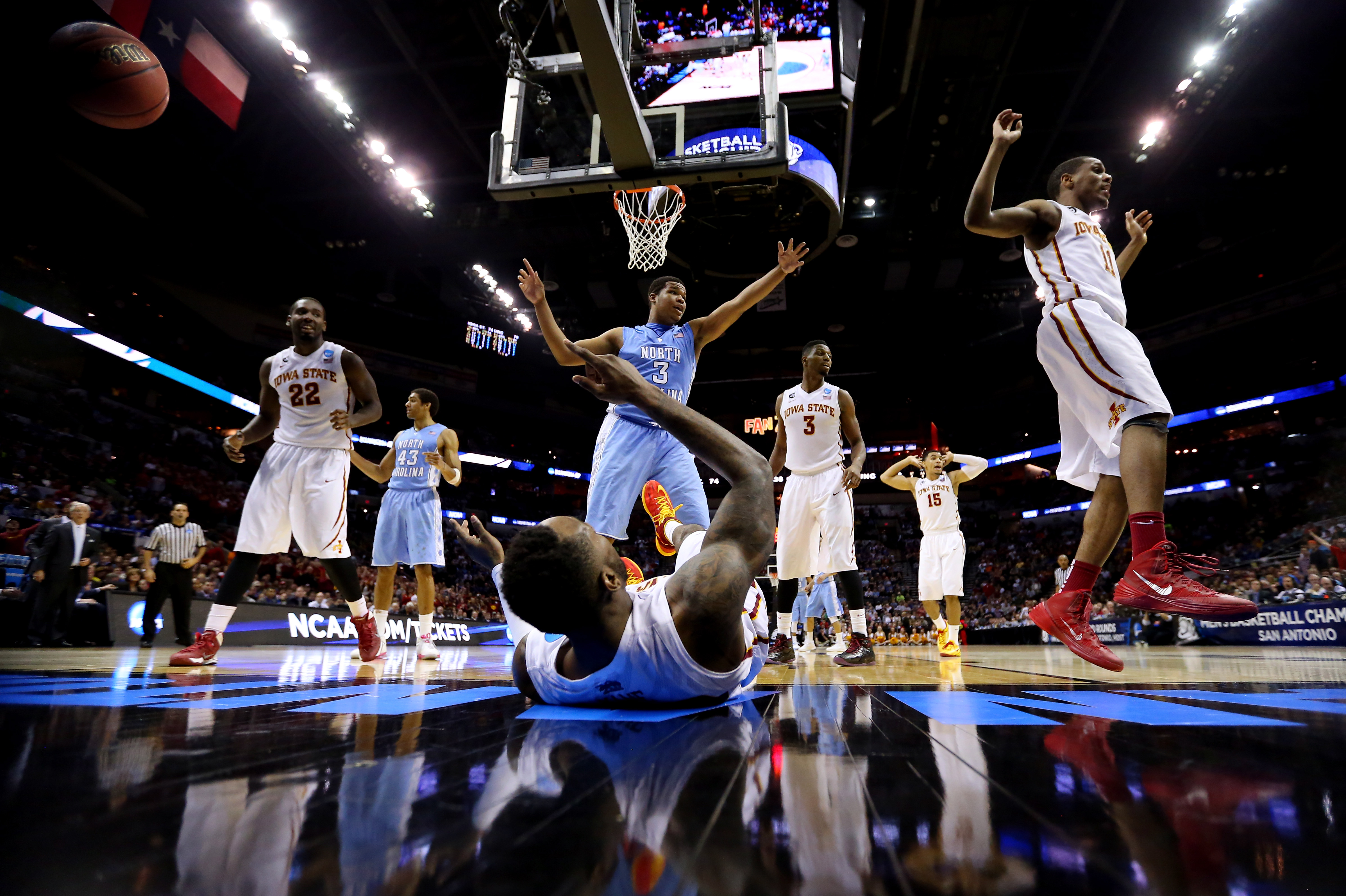 Kennedy Meeks of the North Carolina Tar Heels, center, reacts as DeAndre Kane of the Iowa State Cyclones falls underneath the basket at the AT&T Center in San Antonio on March 23, 2014
