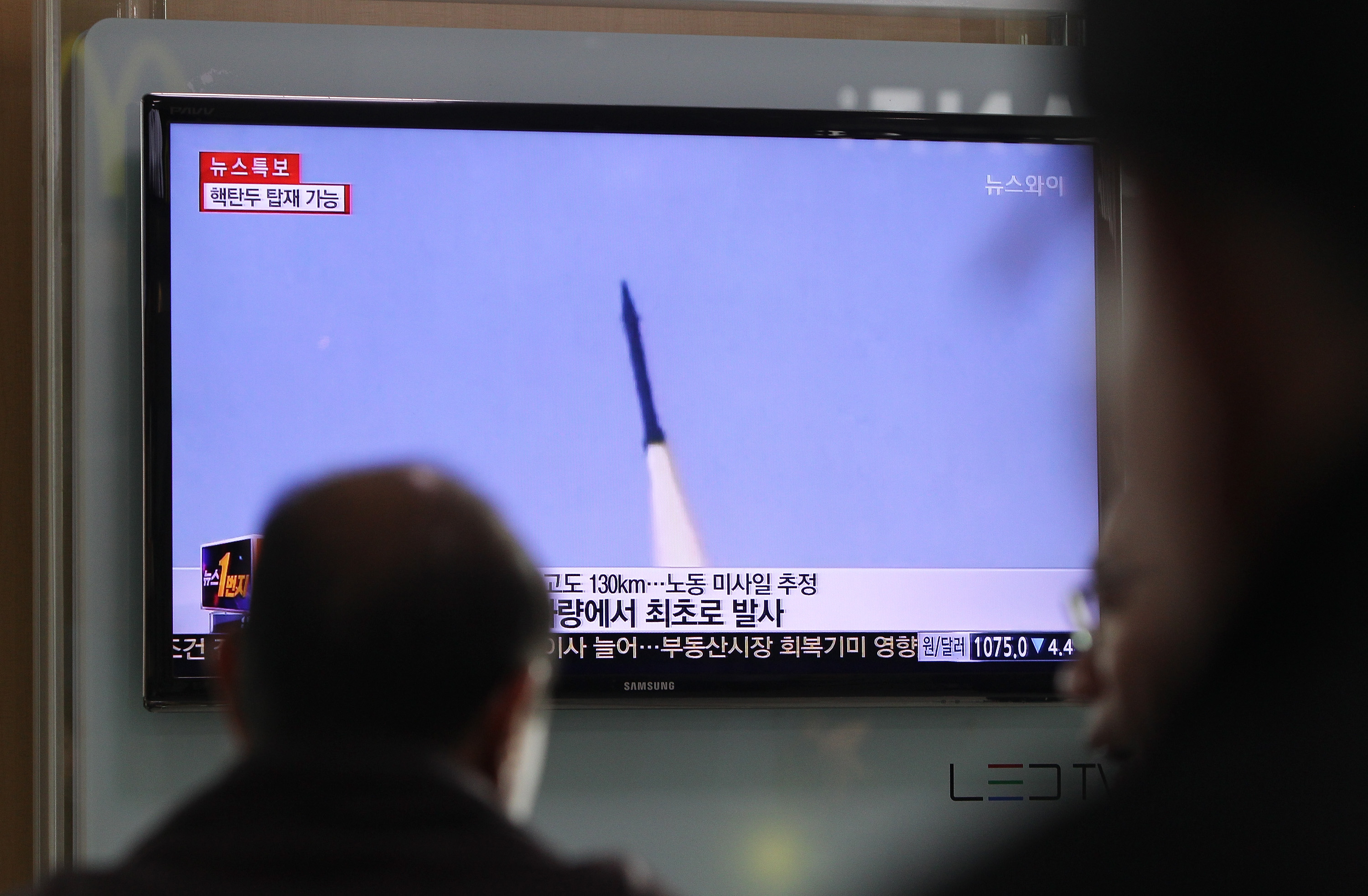 Commuters pause to watch a television broadcast reporting the North Korean missile launch at Seoul Railway Station on March 26, 2014.