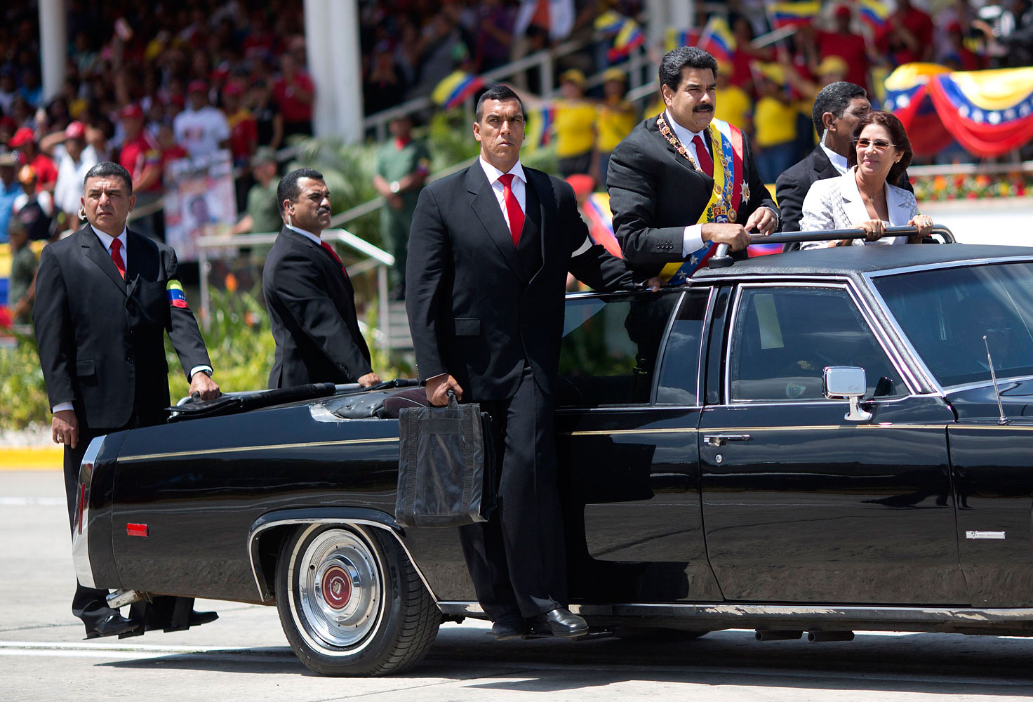 Venezuela's President Nicolas Maduro stands in a convertible limousine next to first lady Cilia Flores as security guards stand on the sides of the car during a military parade commemorating the one year anniversary of the death of Venezuela's former President Hugo Chavez in Caracas, March 5, 2014.
